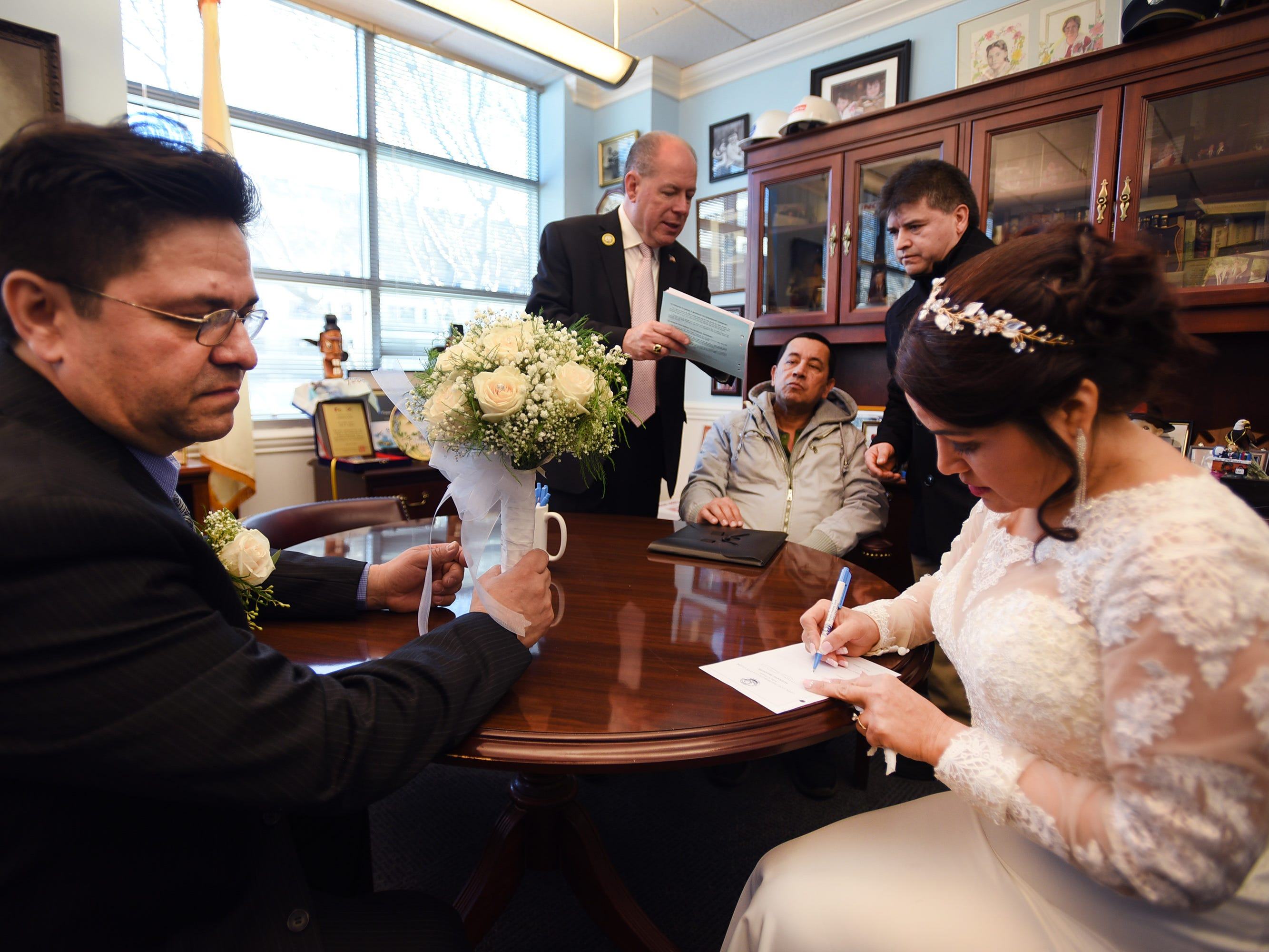 Gloria Gallego and Alexander Gutierrez of Englewood, sign  for their marriage certificate as Bergen County Clerk John S. Hogan explains to their witnesses in Hogan's office at Bergen County Clerk's Office prior to their wedding ceremony, located at Bergen County Plaza in Hackensack on 02/14/19.