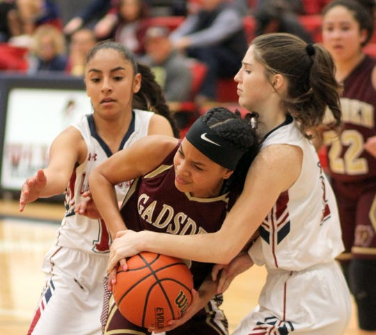 Lady 'Cat sophomores Jasmine Lopez (left) and Sierra Manos (right) trap Gadsden's LaDajah Lara during Tuesday's 56-43 Lady 'Cat victory at Deming High School.