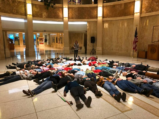 "Student advocates for new gun safety regulations hold a silent ""lie-in"" protest in the state Capitol in Santa Fe, N.M., on Wednesday, Feb. 13, 2019, in anticipation of the anniversary Thursday of the mass shooting at Marjory Stoneman Douglas High School in Parkland, Fla. Some wore T-shirts bearing the names of individuals killed in Parkland. The New Mexico House of Representatives was poised to vote on a bill that would make it easier to take guns away from people who may be suicidal or bent on violence."