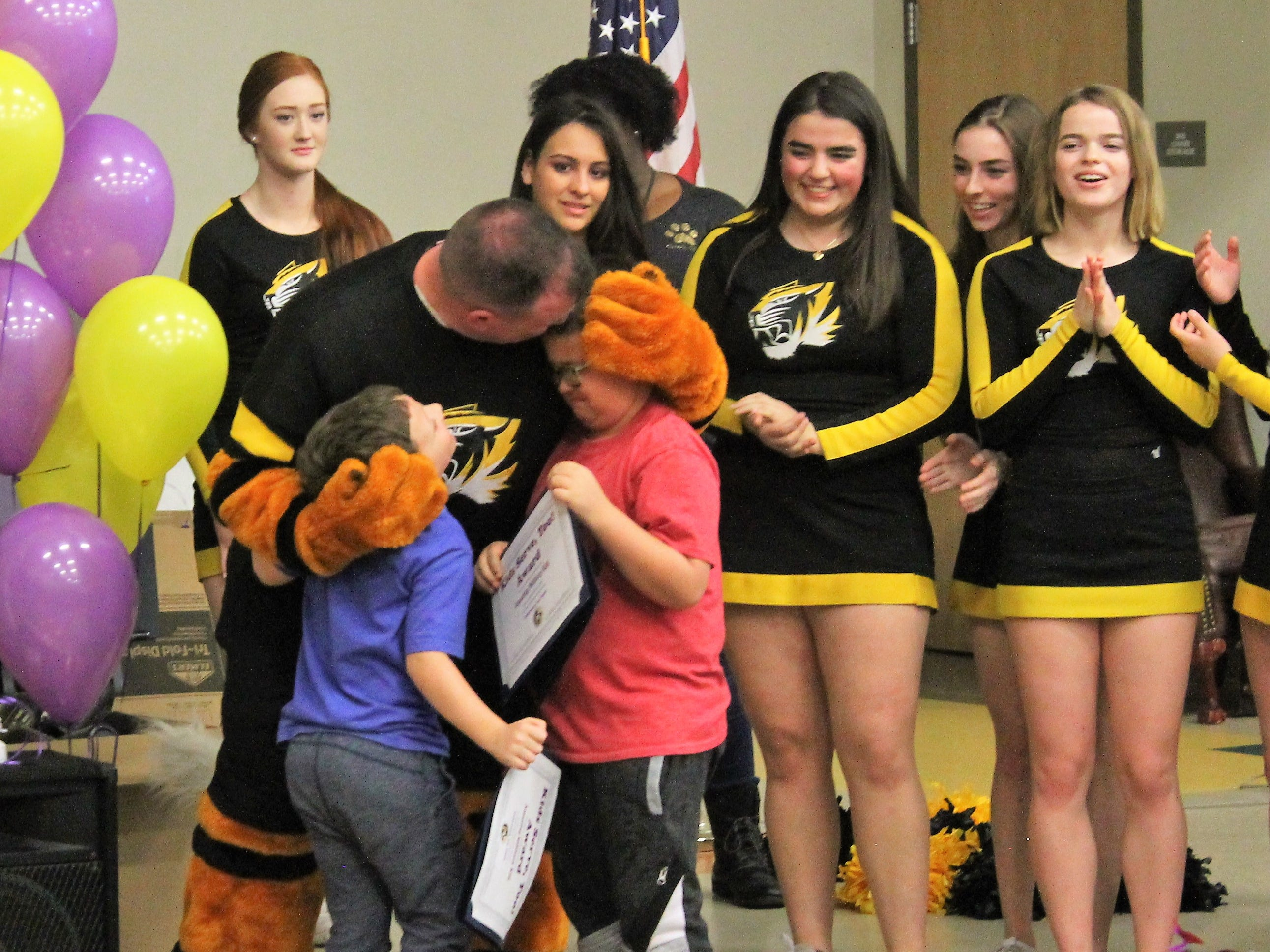 Ethan Scott who was dressed as the Alamogordo High School Tiger mascot revealed himself to his sons Dominic and Corben Scott at a Desert Star Elementary School assembly Feb. 14.