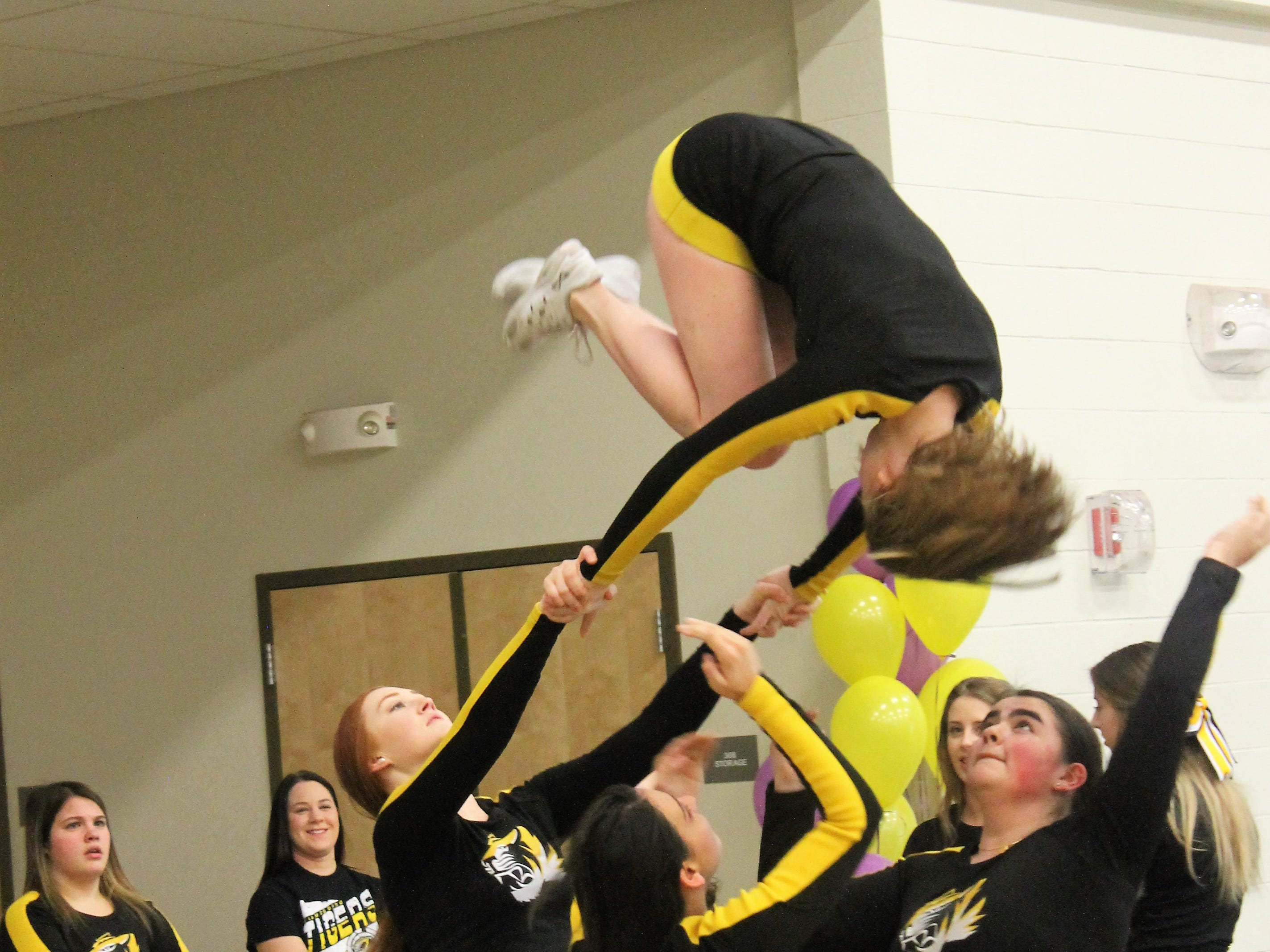An AHS cheerleader flips out of a tower at a Desert Star Elementary School assembly Feb. 14.