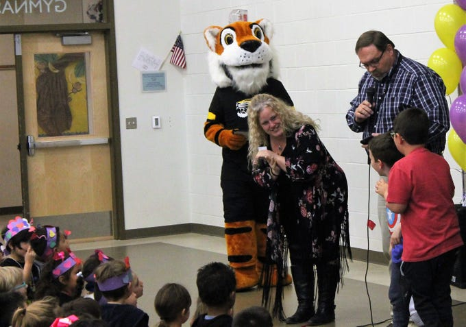 Desert Star Elementary Principal Kaye Crecelius  greets Corben and Dominic Scott at an assembly Feb. 14. The Scotts were given a Kids Serve, Too award. Announcing the winners was Alamogordo Public Schools Chief of Staff Doyle Syling.