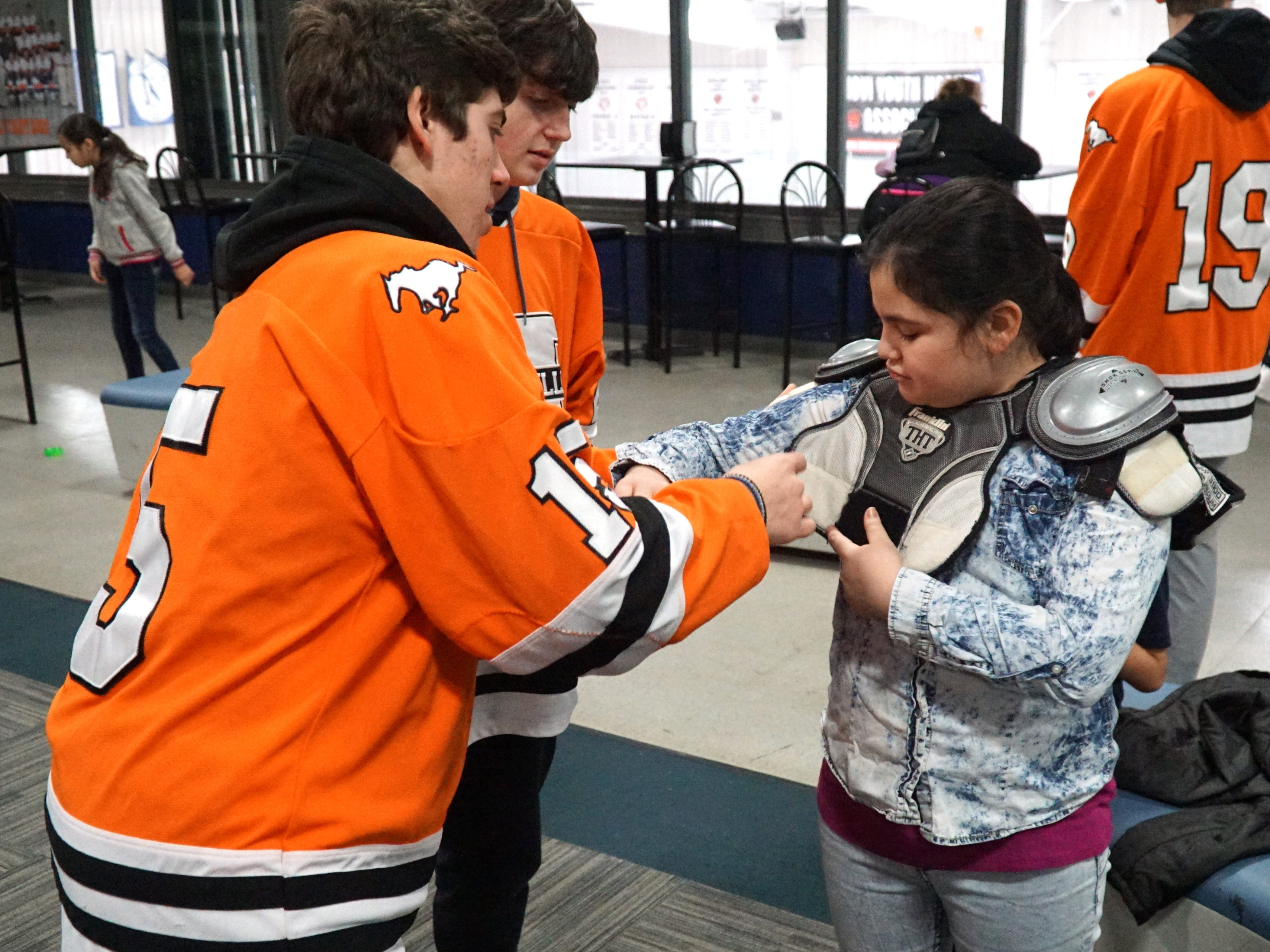 Northville varsity hockey team member Ilias Vrahnos helps to get Neinas Elementary's Maribel Madrigal, 10, into some shoulder pads as the visitors from Detroit see what it's like to get dressed for a hockey game on Feb. 13.