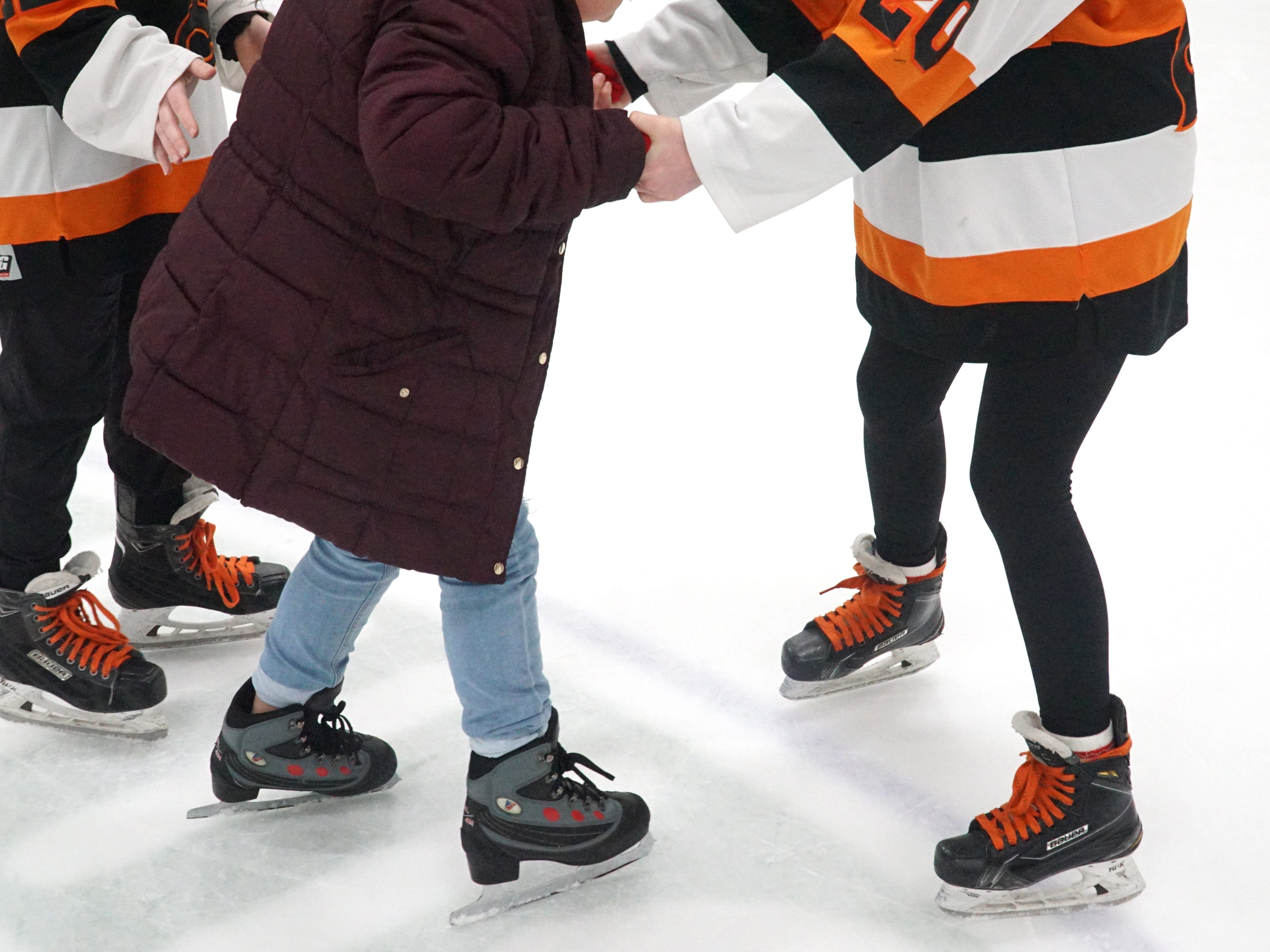 A pair of Mustangs help a Neinas visitor around the surface of the Novi Ice Arena on Feb. 13.