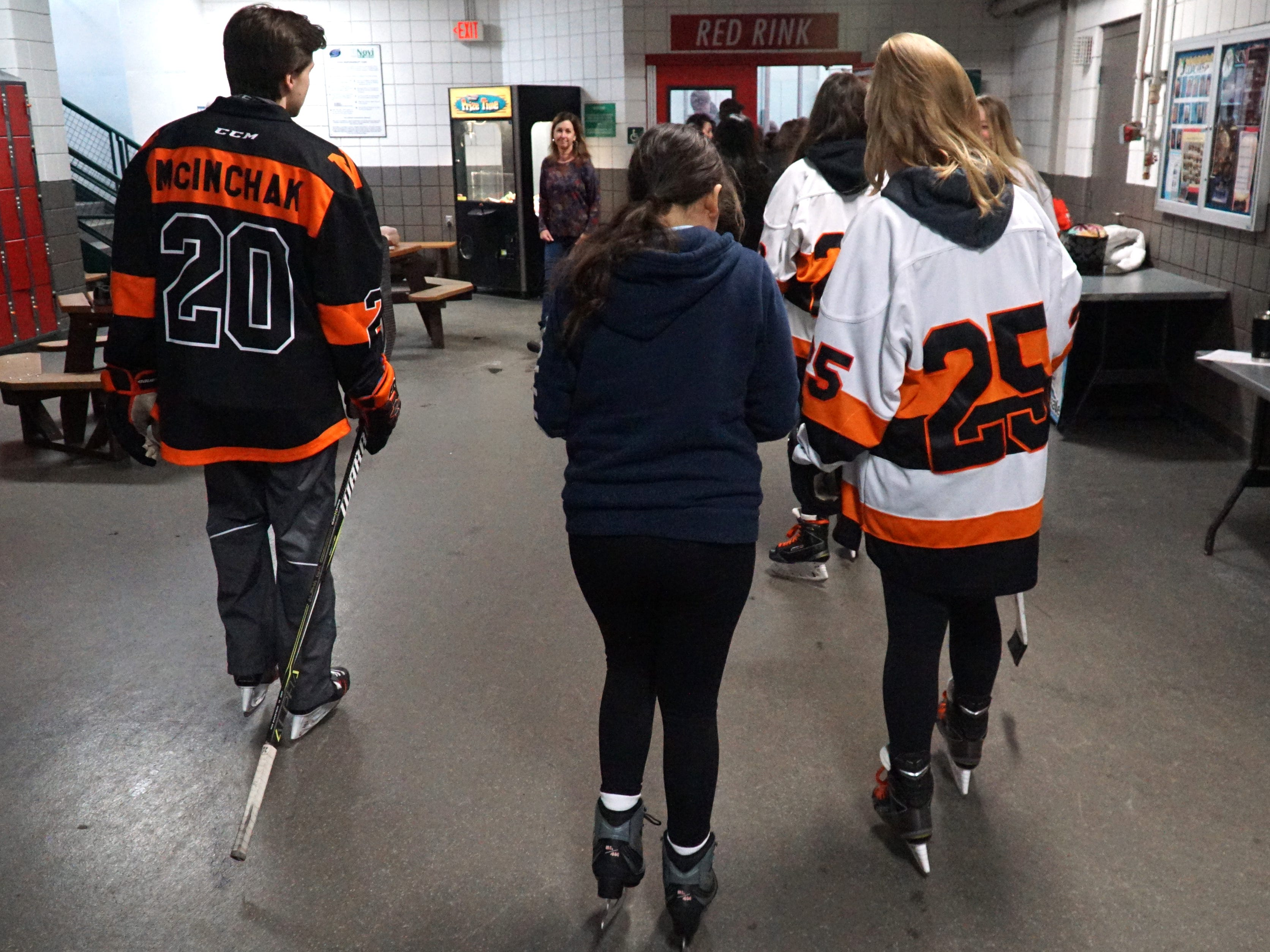 Northville High school varisty team players guide their visitors to the ice.