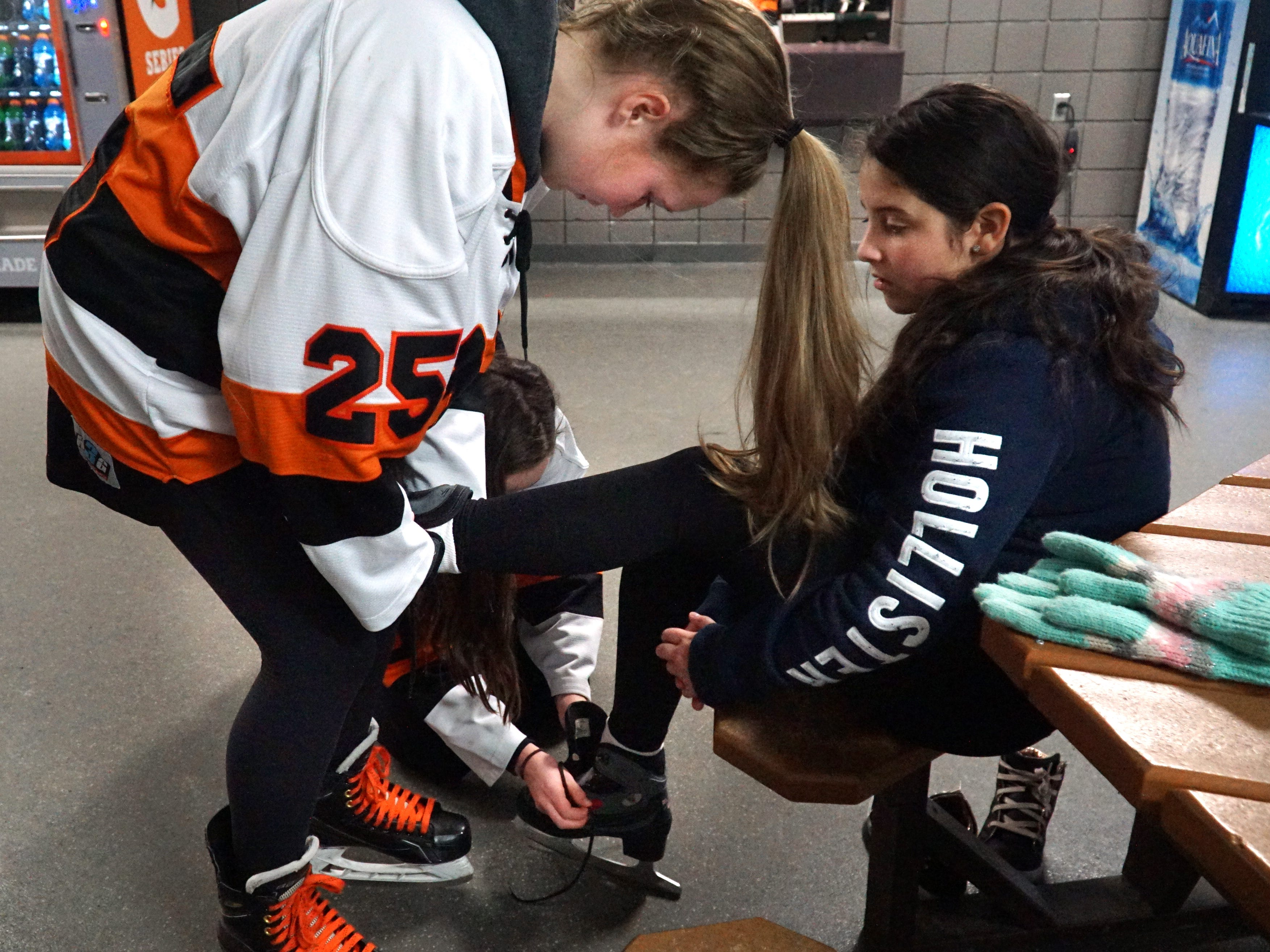 Northville varsity girls hockey team members Brooke Hanson, left, and Grace Lapinski (partially hidden) help to lace up the skates of Neinas Elementary student Maria Salcido, 10, as the Northville schools hockey teams welcomed visitors from Detroit on Feb. 13.