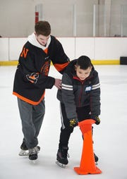 Neinas Elementary student Anthony Florentin is helped around Novi Ice Arena by Northville Mustang Jake McNeil on Feb. 13.