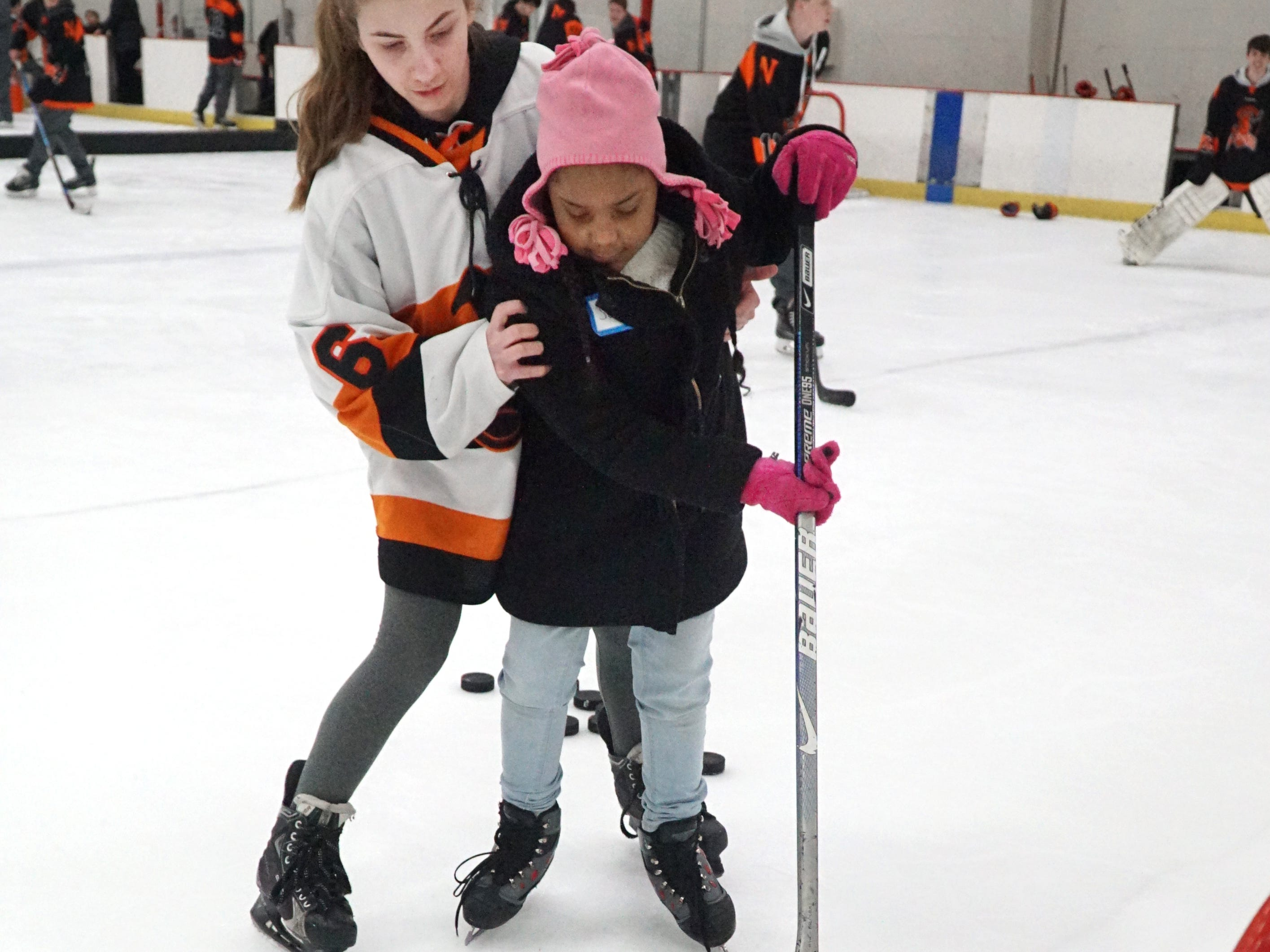 Northville High School hockey player Kalliopi Brahnos, a freshman, helps Neinas Elementary visitor Senaya Bailey, 9, with her puck-shooting abilities during a Feb. 13 session at the Novi Ice Arena.