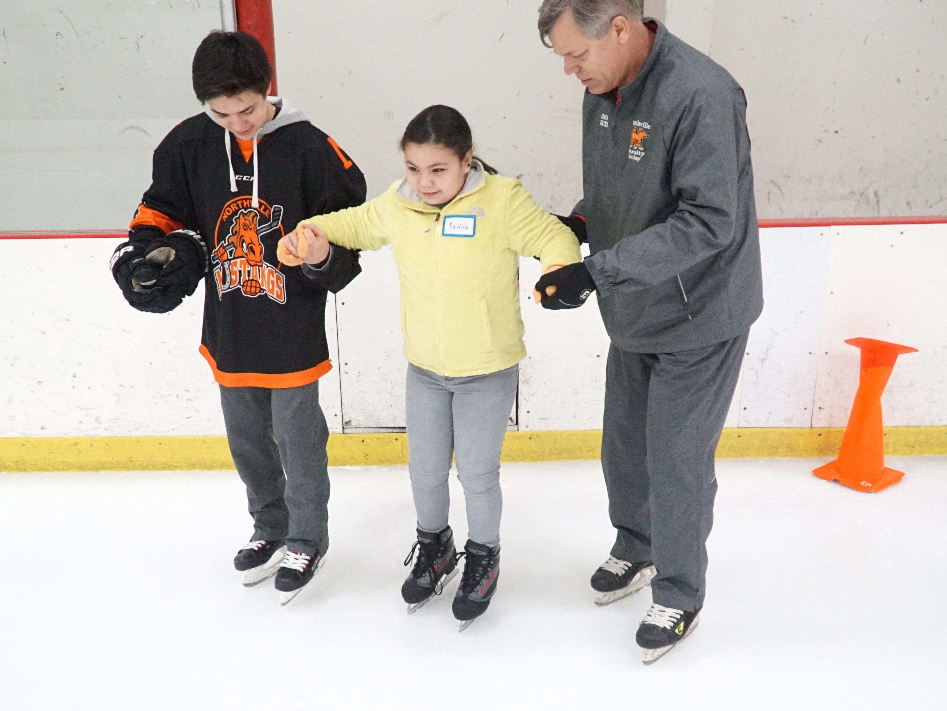 Northville High School varsity hockey coach John Gates and Mustang Derek Fiebig help Neinas Elementary visitor Yadira Hernandez, center, around the ice on Feb. 13.