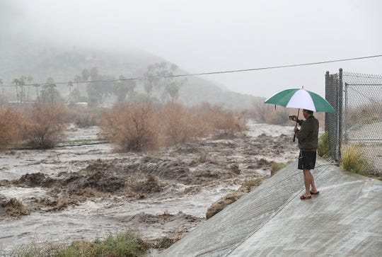 A man records the water flowing along the Coachella Valley stormwater channel and closes Araby Drive in Palm Springs during heavy rains, February 14, 2019.