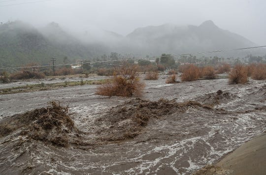A torrent of water flows along the Coachella Valley stormwater channel and closes Araby Drive in Palm Springs during heavy rains, February 14, 2019.