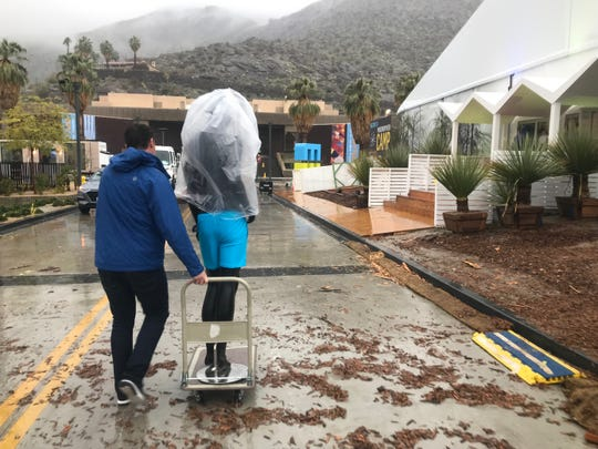 A Modernism Week crew member continues to prep for the opening of the event's CAMP headquarters despite Thursday's rain, Feb. 14, 2019.