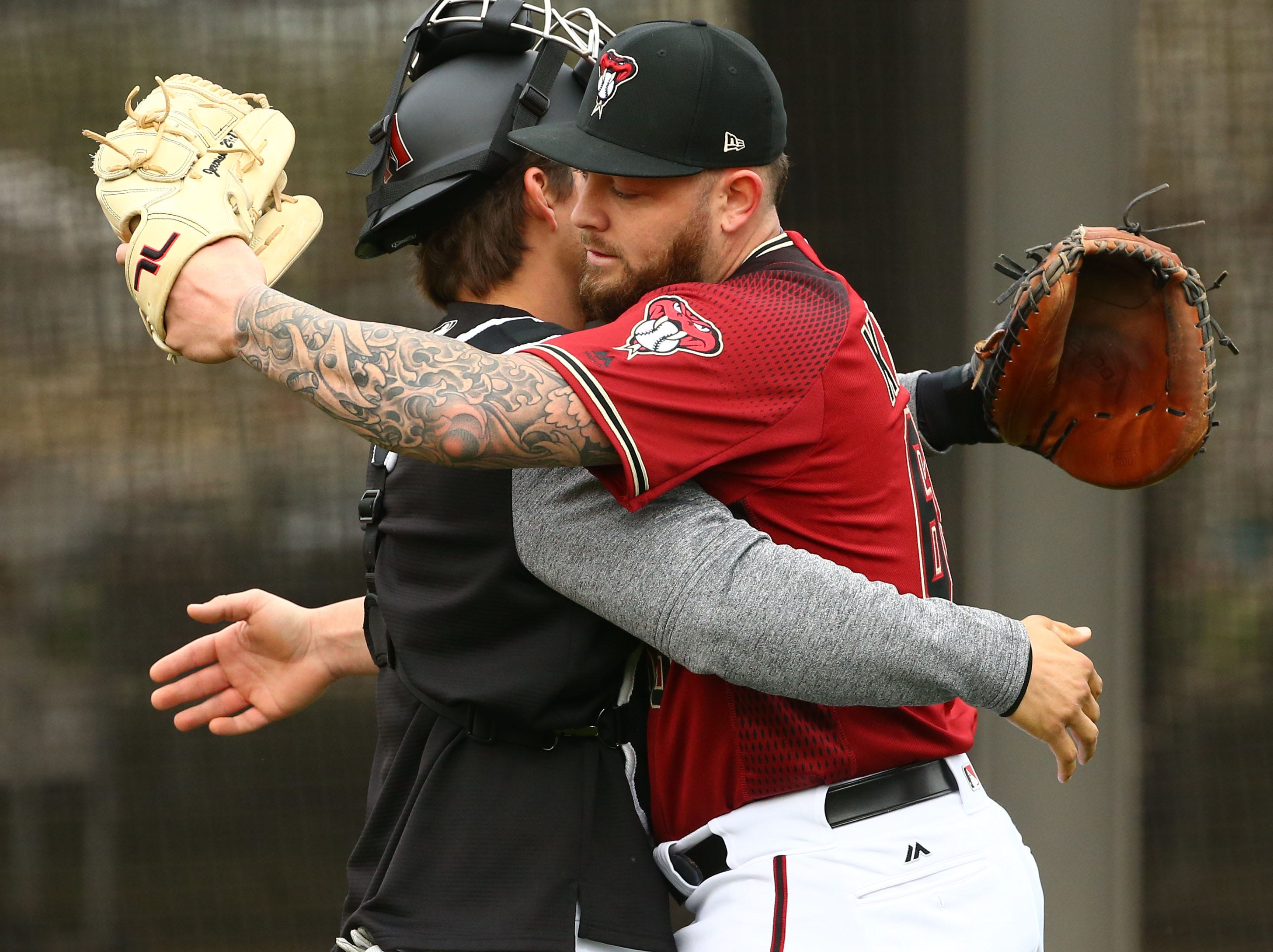Arizona Diamondbacks pitcher Joey Krehbiel hugs his catcher after his bullpen session during the first day of spring training workouts on Feb. 13 at Salt River Fields in Scottsdale.