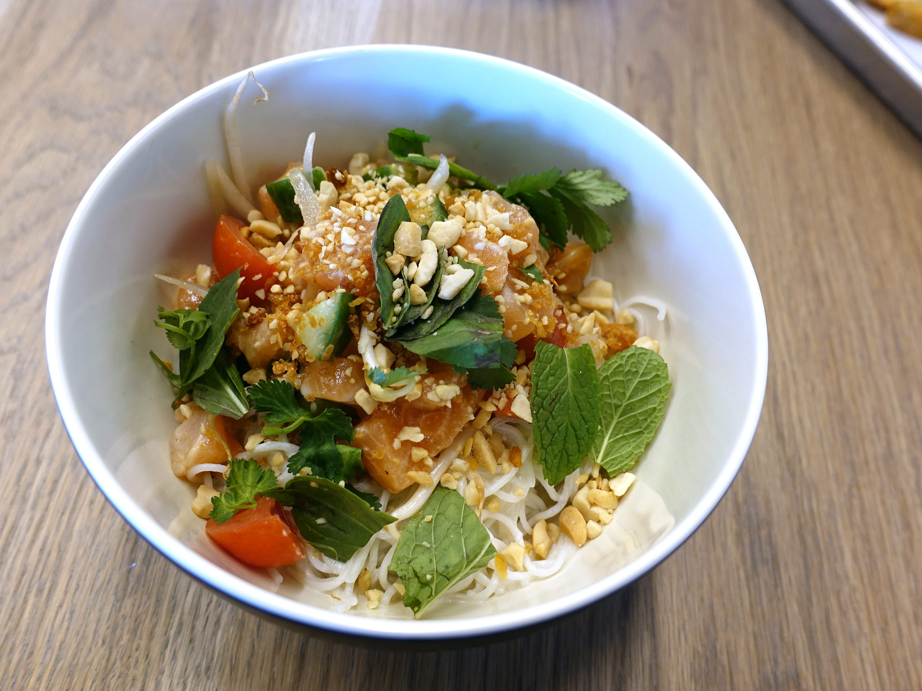 Coconut noodle bowl with salmon poke, rice noodles, cucumber, tomato, sprouts, fried garlic, tamarind vinaigrette, coconut broth and fresh herbs at Chula Seafood Uptown in Phoenix.