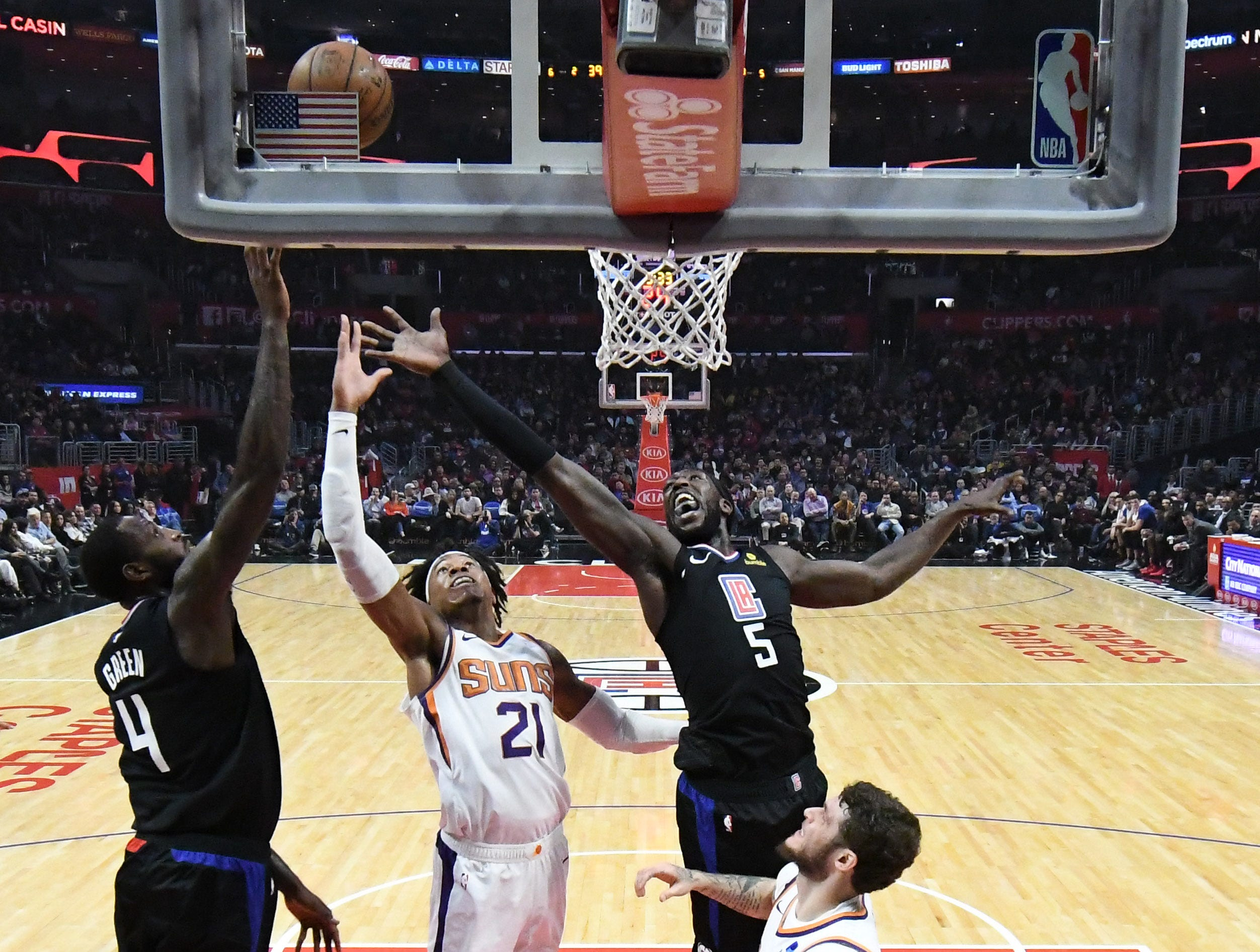 Feb 13, 2019; Los Angeles, CA, USA; Phoenix Suns forward Richaun Holmes (21) shoots between LA Clippers forward Montrezl Harrell (5) and forward JaMychal Green (4) in the first half at Staples Center. Mandatory Credit: Richard Mackson-USA TODAY Sports