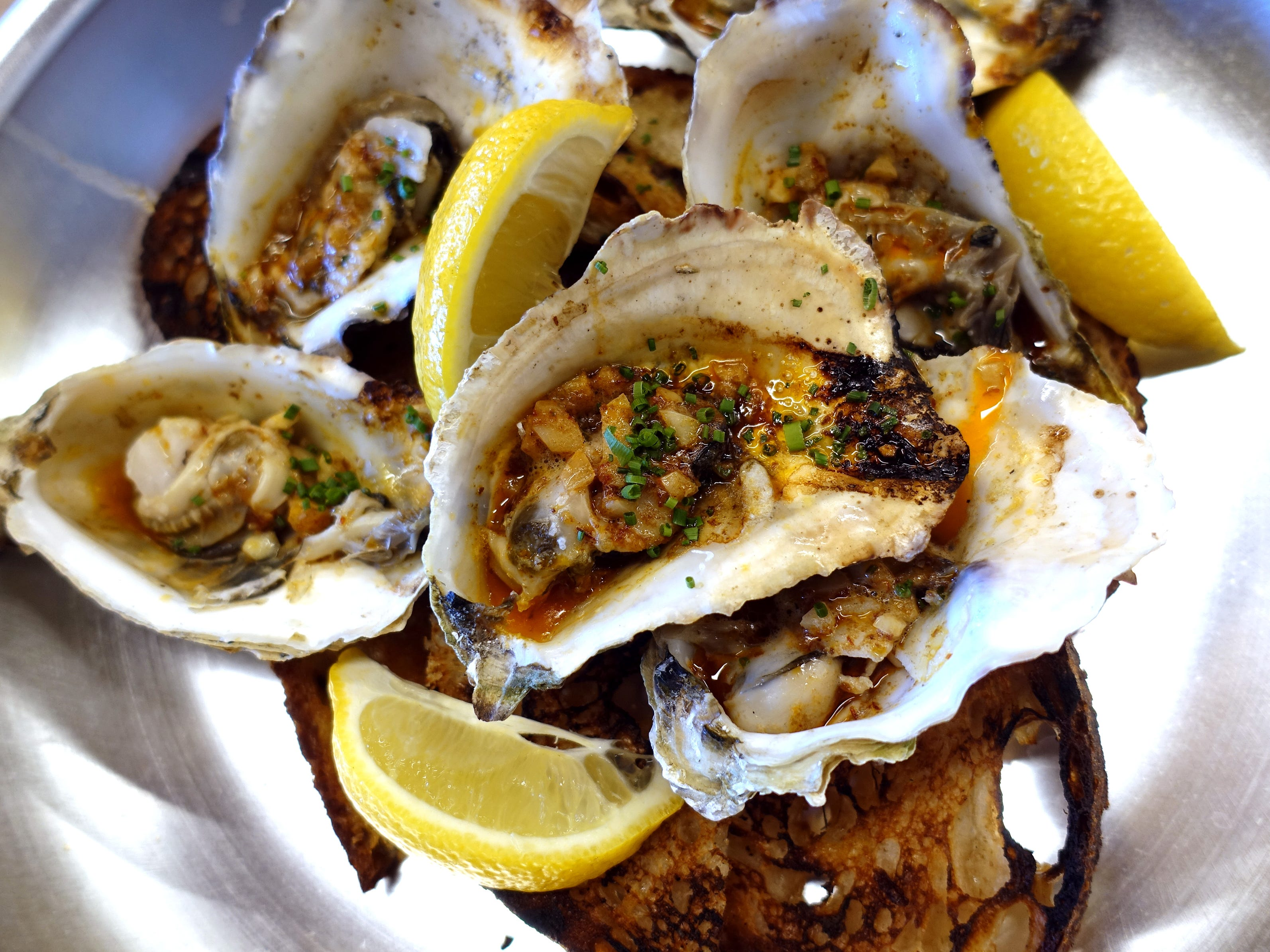 Grilled oysters with chipotle butter and grilled Noble bread at Chula Seafood Uptown in Phoenix.