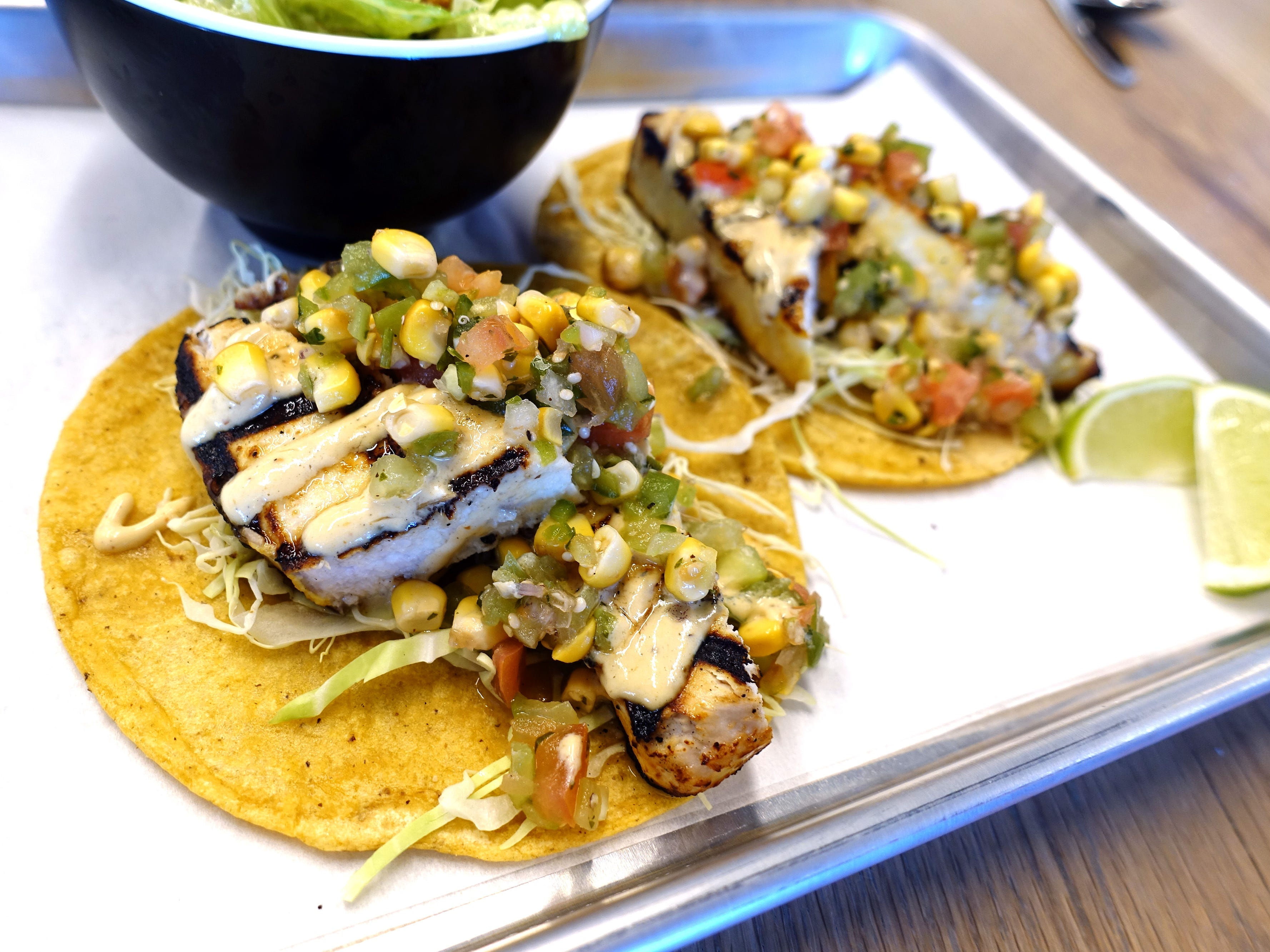 Swordfish tacos with mojo marinated grilled Chula swordfish, smoked corn, tomatillo pico, shredded cabbage and chile crema at Chula Seafood Uptown in Phoenix.