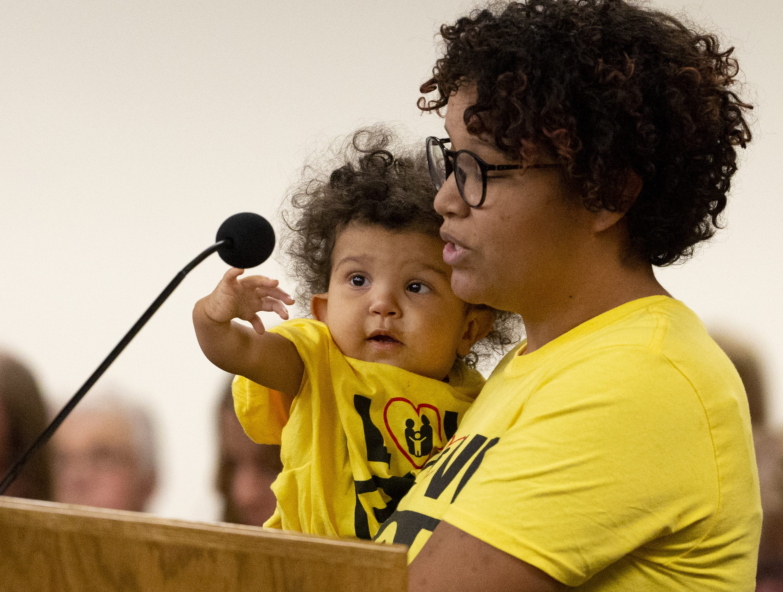 Levi Svedin, 1, reaches for the microphone while his mother, Kayla, speaks in favor of ESA during a hearing on school vouchers in a senate hearing room at the state Capitol in Phoenix on February 13.