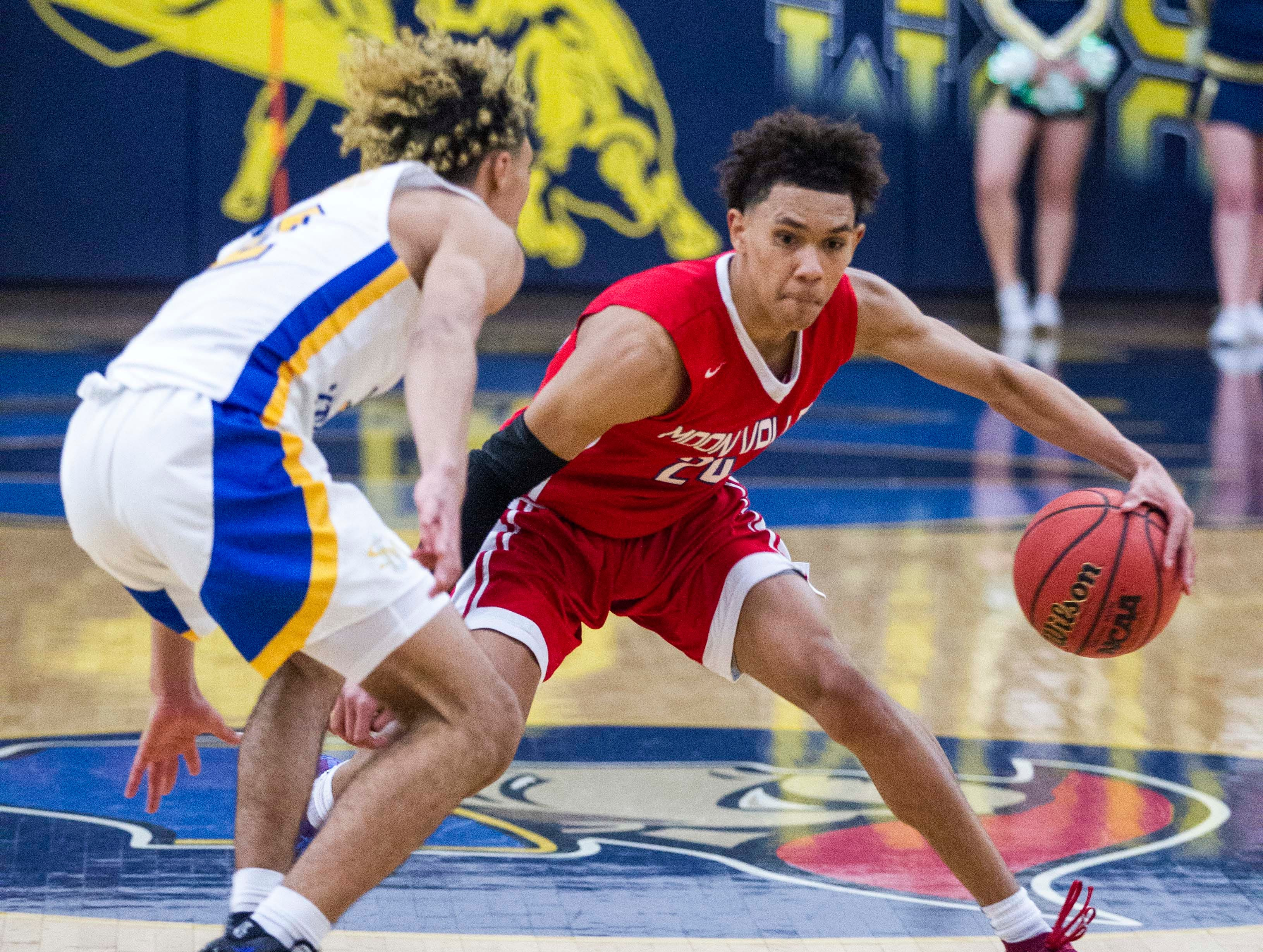 Moon Valley's John Mcknight (20) dribbles against Shadow Mountain's Jaelen House (2) during the first half of their game in Phoenix, Tuesday, Feb .12,  2019.