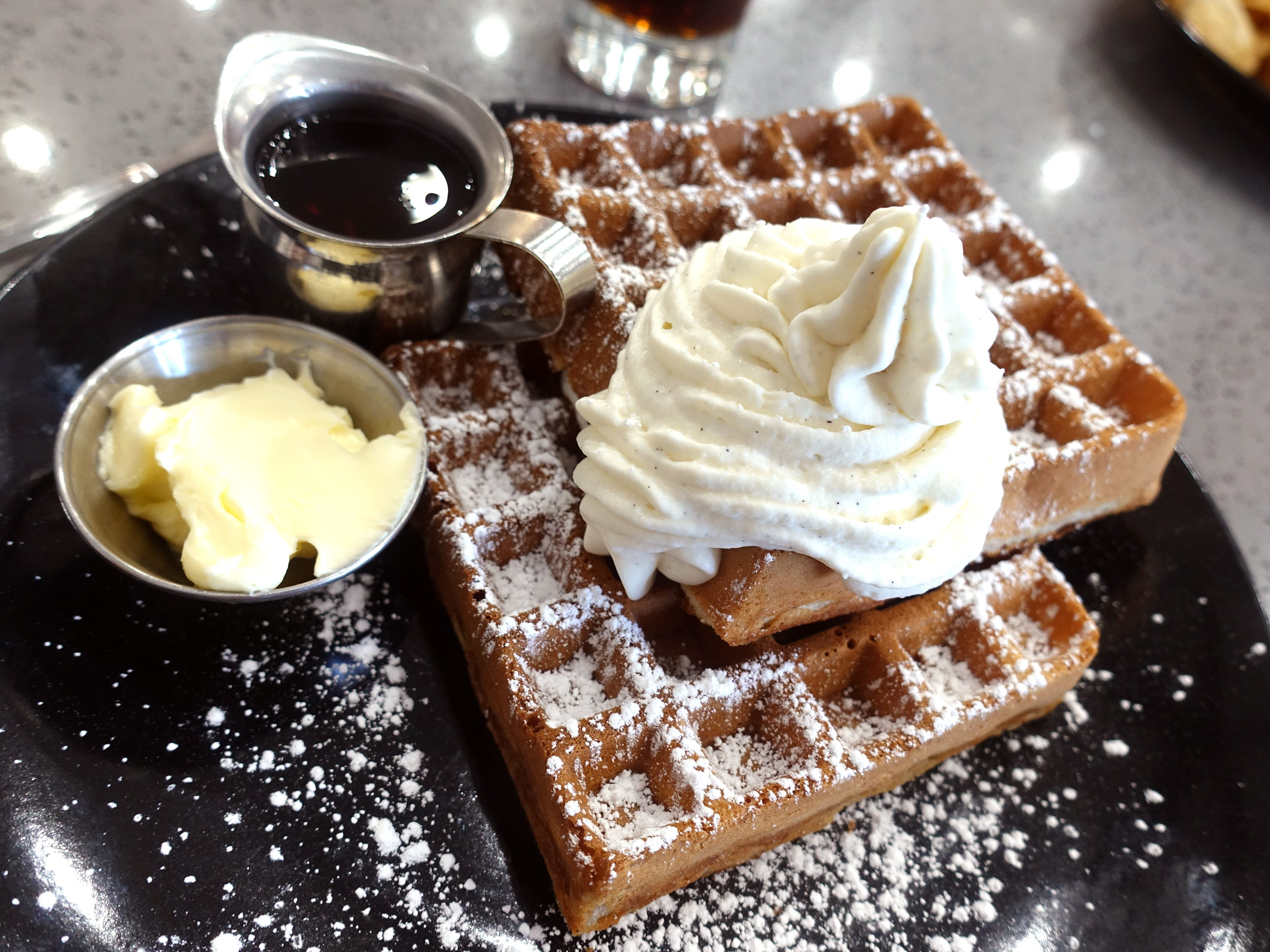 Belgian waffles dolloped with vanilla bean whipped cream at Sweetest Season Artisan Eatery in Tempe.