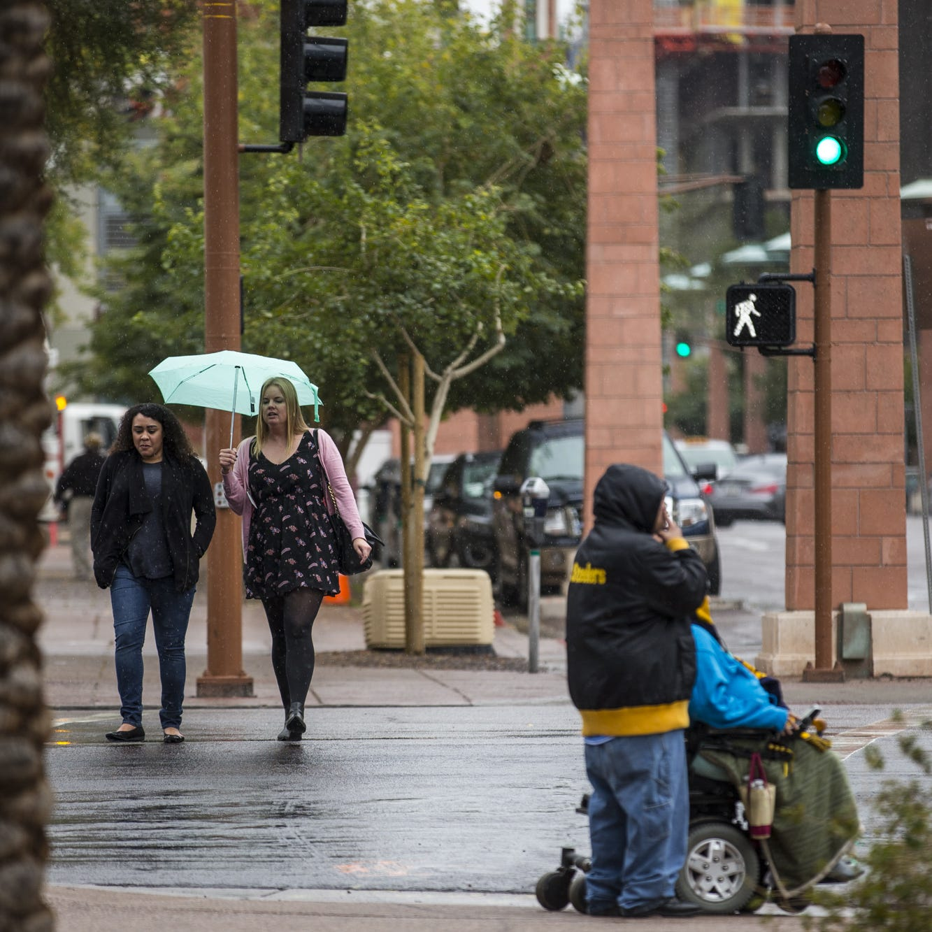 People cross the street in the rain on Thursday, Feb. 14, 2019, in downtown Phoenix.