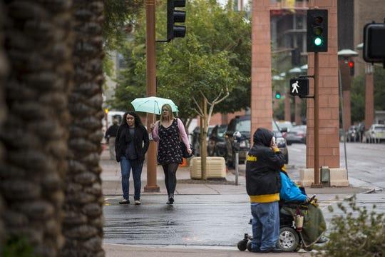 People cross the street in the rain on Thursday, Feb. 14, 2019, in downtown Phoenix.