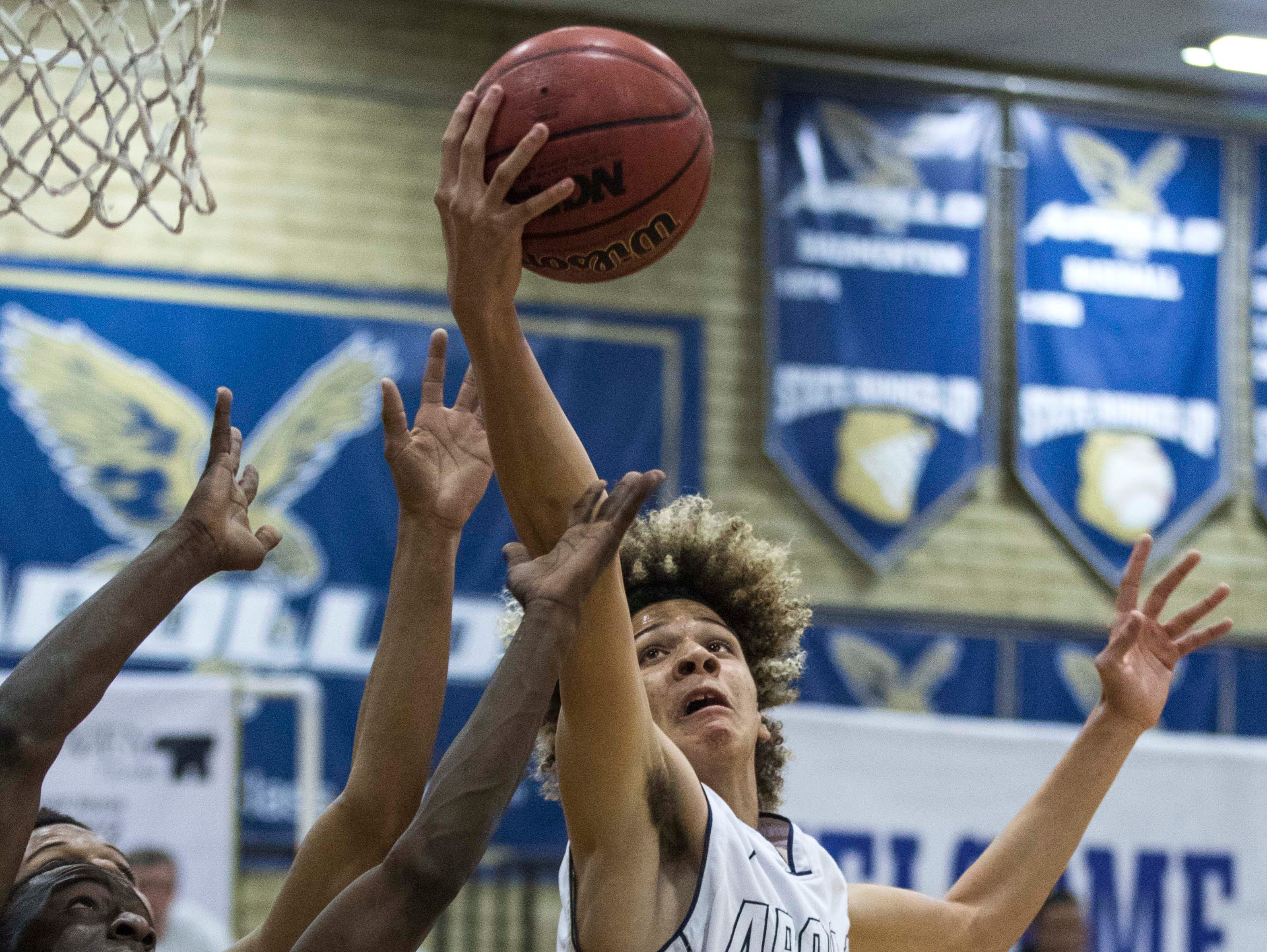 Apollo's Paris Woods (10) pulls down a rebound against South Mountain during the first half of their game in Phoenix, Wednesday, Feb .13,  2019.