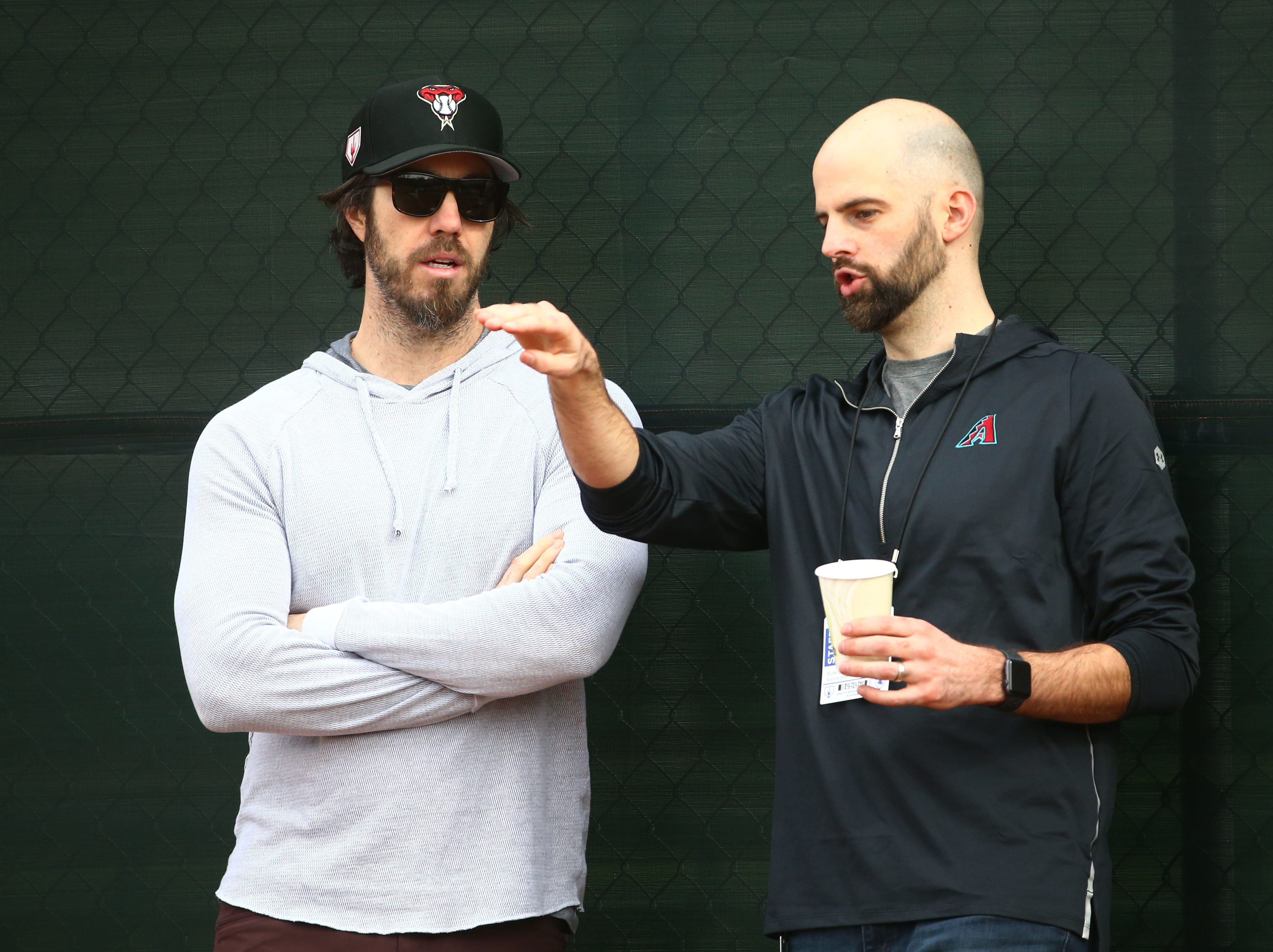Retired pitchers Dan Haren and Burke Badenhop watch the Arizona Diamondbacks bullpen during the first day of spring training workouts on Feb. 13 at Salt River Fields in Scottsdale.
