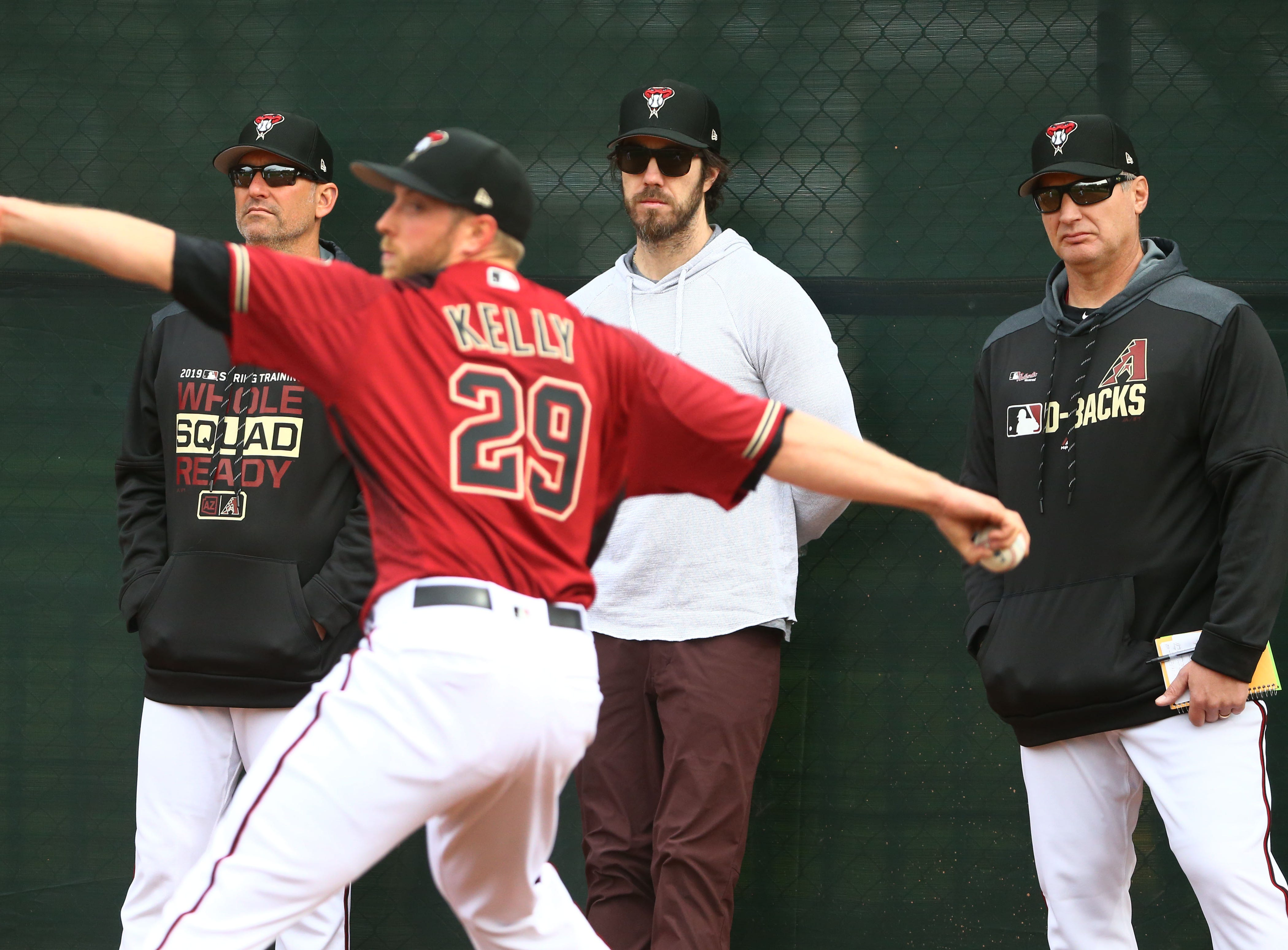 Manager Torey Lovullo and retired pitcher Dan Haren watch Arizona Diamondbacks Merrill Kelly (29) in the  bullpen during the first day of spring training workouts on Feb. 13 at Salt River Fields in Scottsdale.