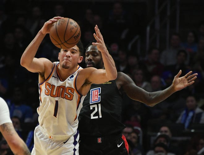 Feb 13, 2019; Los Angeles, CA, USA; Phoenix Suns guard Devin Booker (1) grabs the ball in front of LA Clippers guard Patrick Beverley (21) in the second half at Staples Center. Mandatory Credit: Richard Mackson-USA TODAY Sports