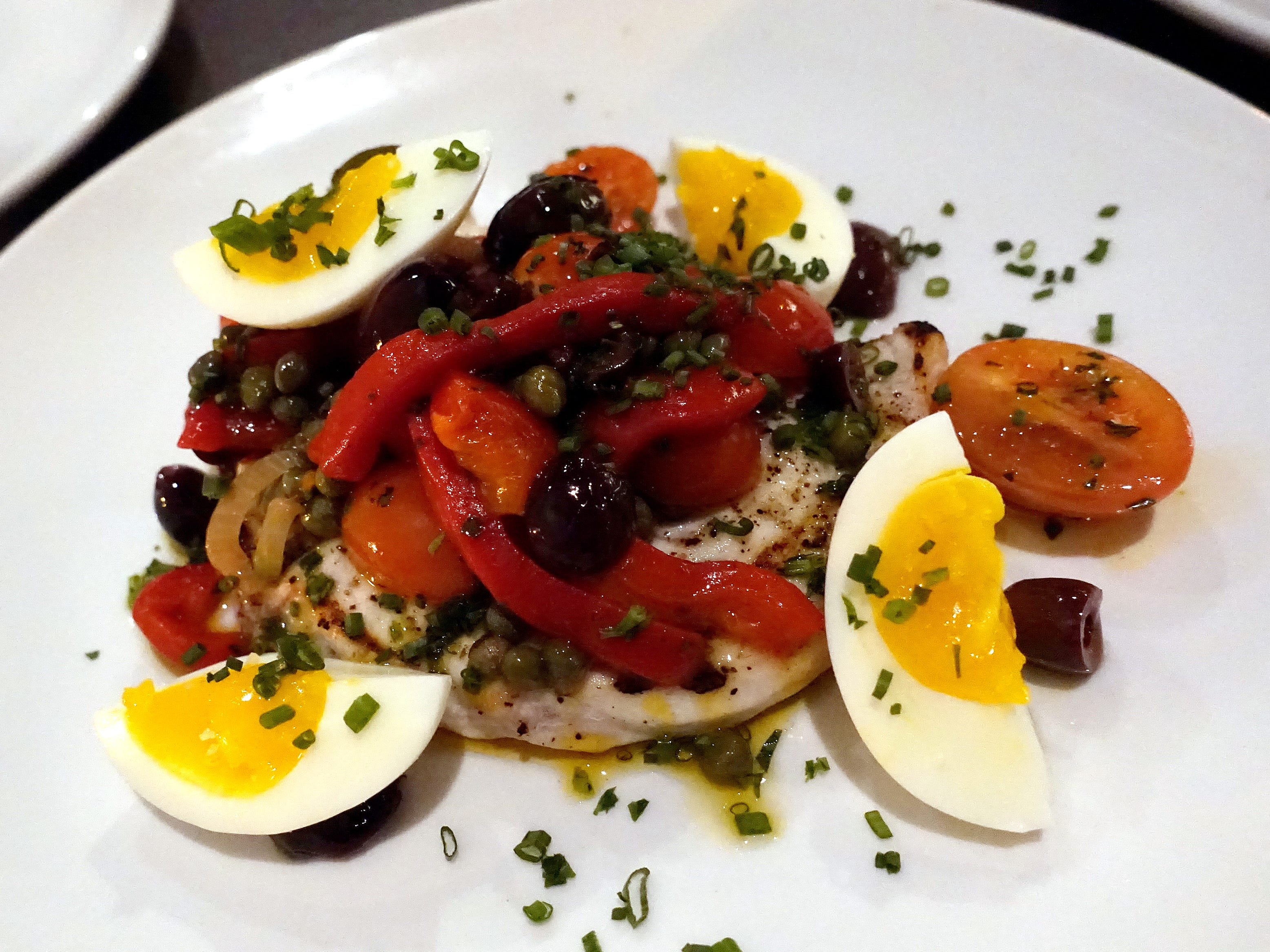 Grilled Chula swordfish with roasted peppers, tomatoes, capers, olives and soft boiled egg at Hush Public House in Scottsdale.