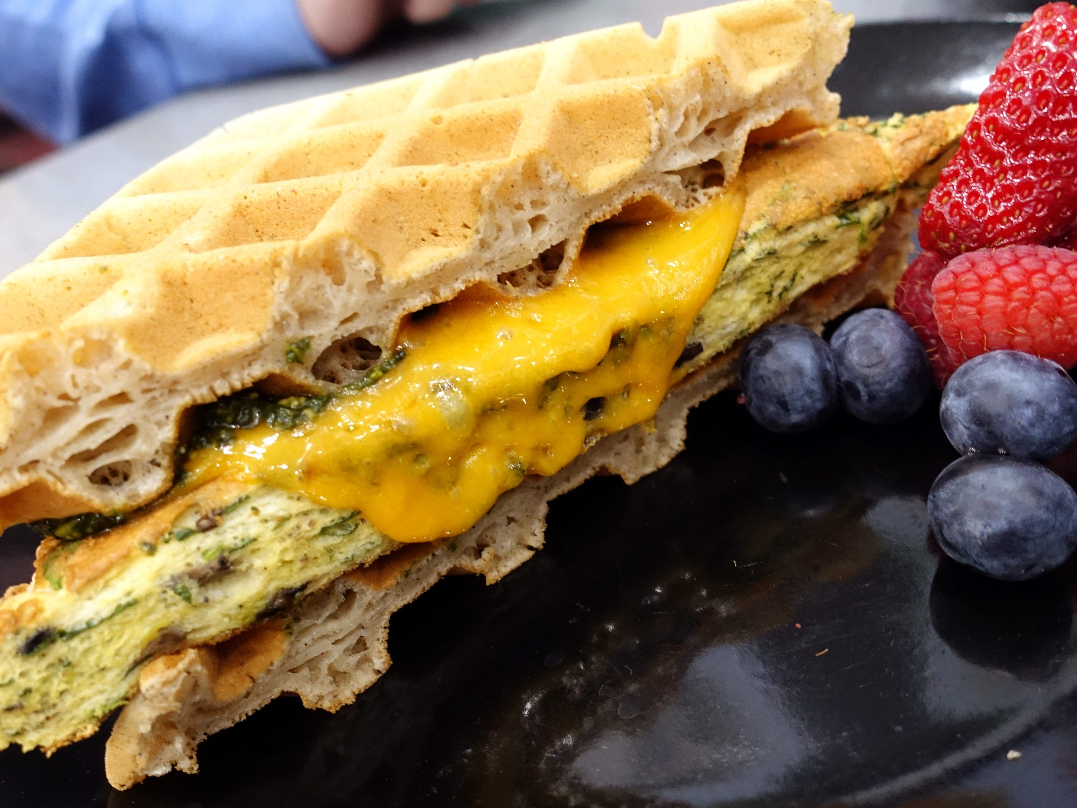 Spin & Shrooms breakfast sandwich with spinach and mushroom souffle baked egg, cheddar cheese and pesto on waffles at Sweetest Season Artisan Eatery in Tempe.