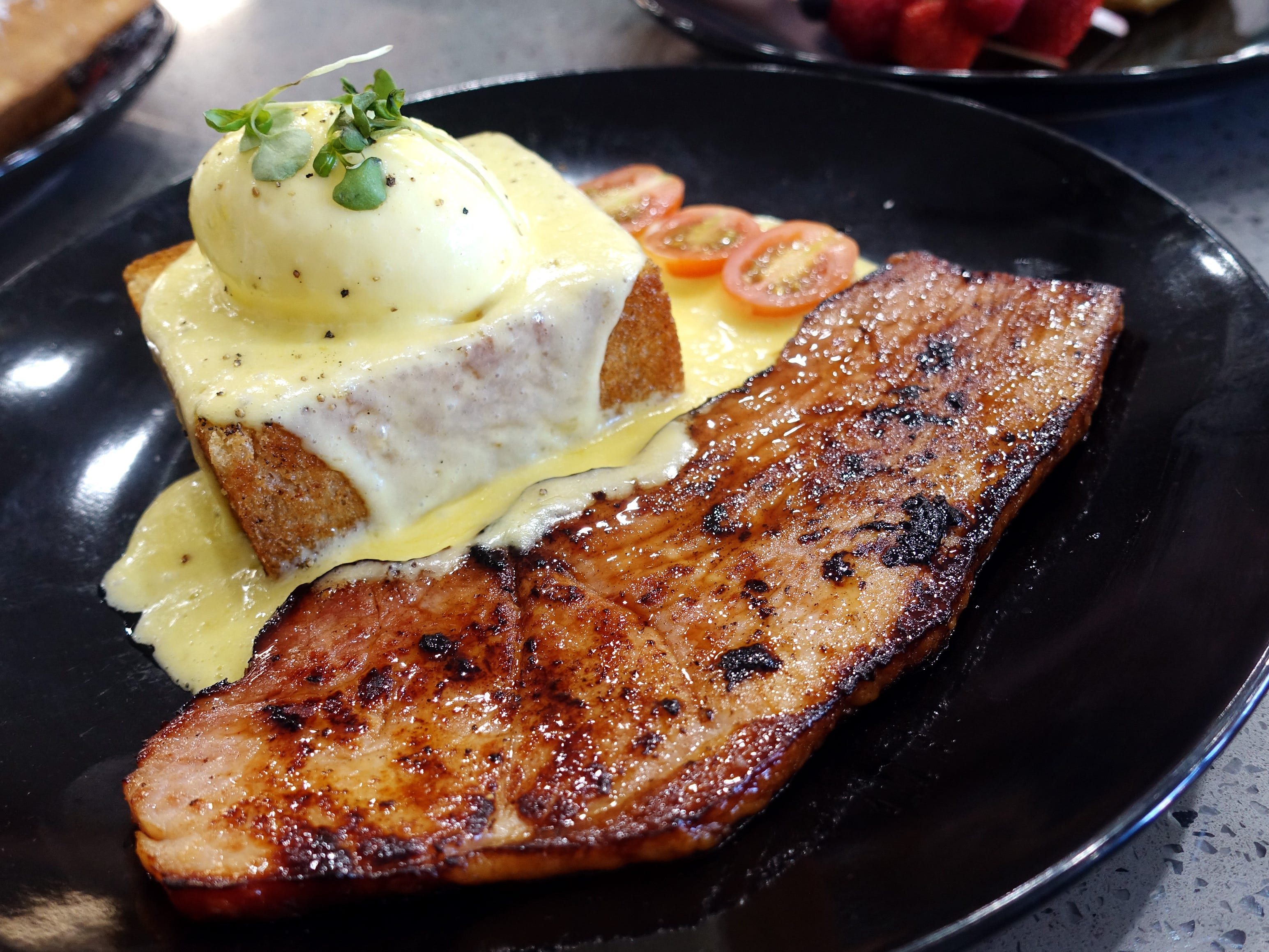 Season's Benedict with buttered toast crouton, soft-boiled egg, grilled ham steak, fresh tomatoes and Hollandaise at Sweetest Season Artisan Eatery in Tempe.