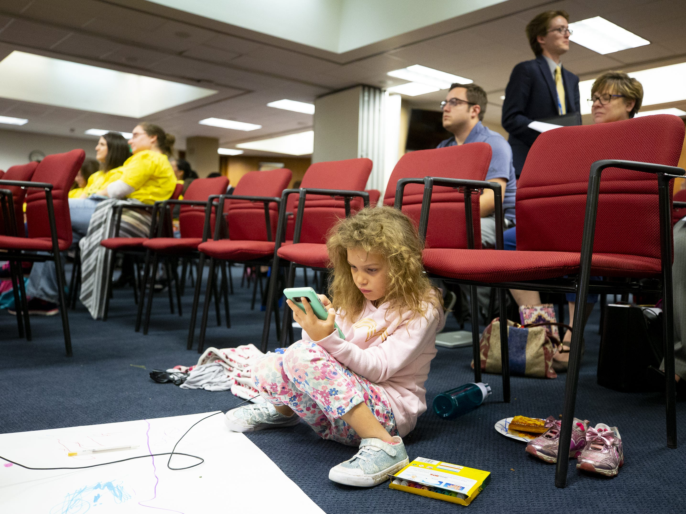 Sarah Svedin, of Queen Creek, keeps herself entertained during a hearing on school vouchers in a senate hearing room at the state Capitol in Phoenix on February 13.