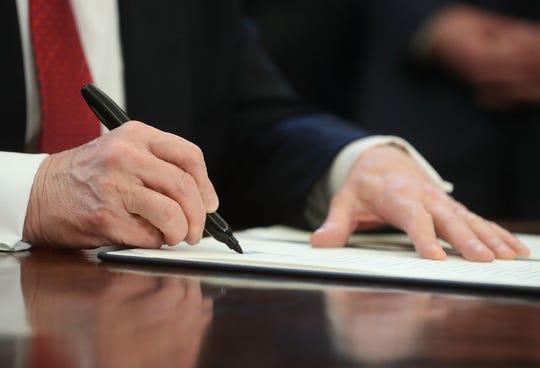 Trump firma una orden ejecutiva.