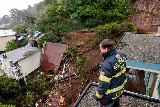 El bombero/paramédico Patrick Young del Departamento de Bomberos del Sur de Marin observa las secuelas de un alud que destruyó tres casas en una ladera en Sausalito, California, el jueves 14 de febrero de 2019.