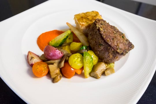 A filet mignon entree with carrot puree, fresh vegetables and potato pave are arranged on a plate in the Culinary Institute of Michigan's COURSES restaurant.