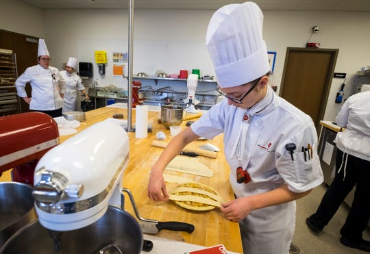 Culinary Institute of Michigan student Fiona Irish, 19, sets strips of crust to form a lattice on top of an apple pie Wednesday, Feb. 13, 2019 in one of the school's labs. Irish said she enjoys the focus that comes with baking, with her favorite treat to make being macaroons.
