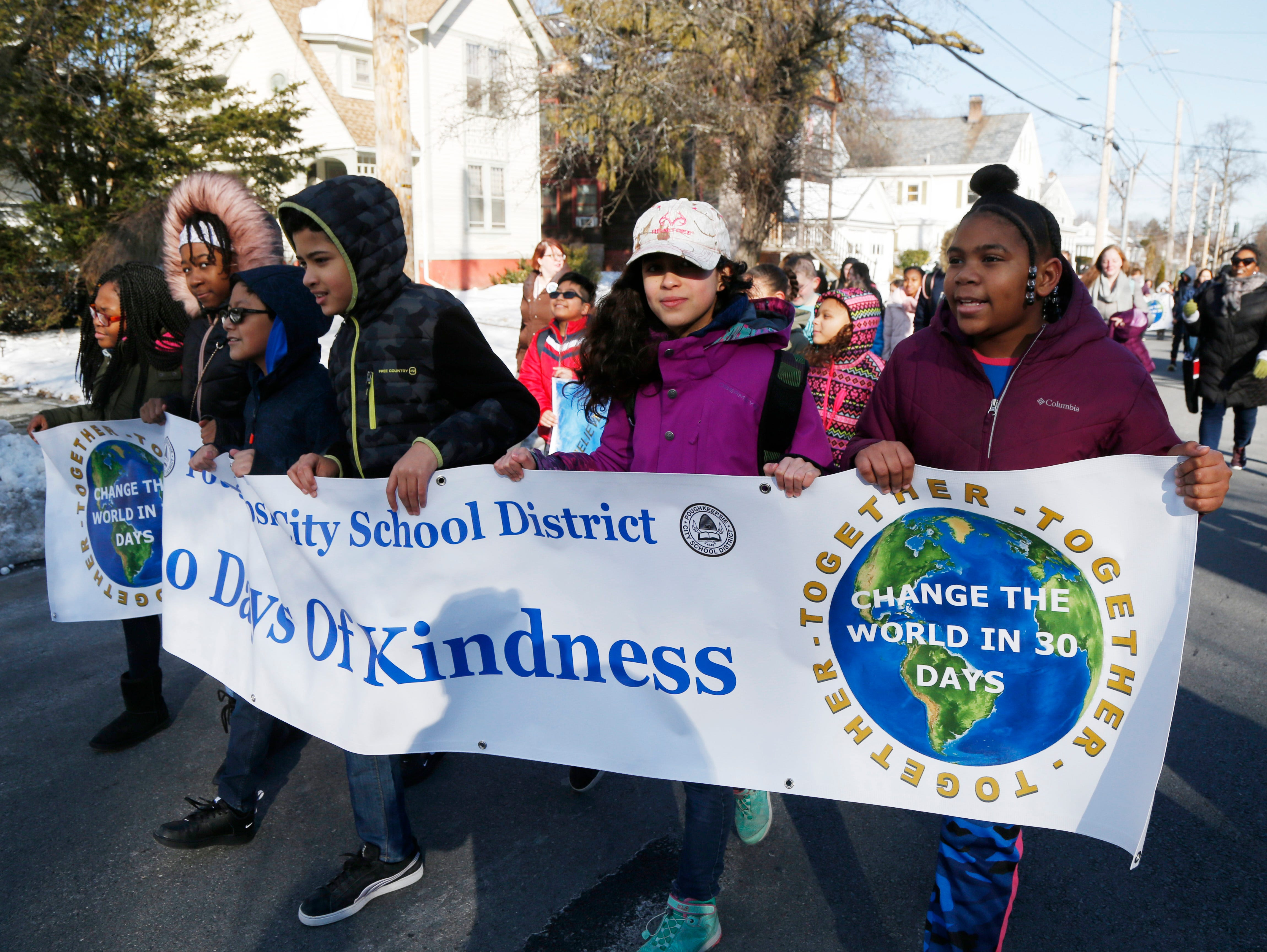 Leading the City of Poughkeepsie school district peace walk as part of Thursday's Martin Luther King Celebration, students from Clinton Elementary School, from left, Kyshina Justus-Gause, Kylee Anglero, Kameron Palmatier, Ian Reyes, Renae Gillette and Leilani Thompson march along South Cherry Street on February 14, 2019.