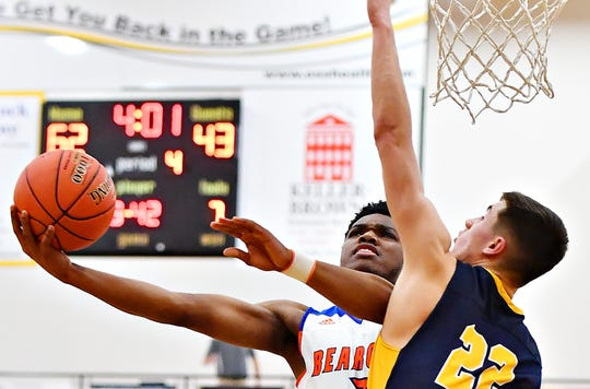 York High's Clovis Gallon Jr, left, takes the ball to the hoop while Littlestown's Logan Collins defends in the York-Adams League tournament semifinals. Gallon Jr. finished seventh in scoring, second in free throw percentage and sixth in 3-pointers in the league, while Collins was second in scoring, first from the line and 20th in 3-pointers. Dawn J. Sagert photo