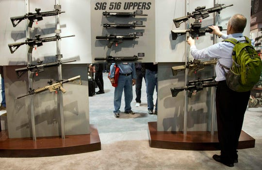 FILE - In this Jan. 15, 2013, file photo, a convention attendee looks through a display of SIG Sauer semiautomatic rifles during the National Shooting Sports Foundation's annual SHOT Show in Las Vegas. Two trade show workers have been arrested on federal weapon charges after the theft of dozens of firearms from the gun industry's biggest annual convention in Las Vegas in January 2019. Both men were arraigned Wednesday, Feb. 13, in U.S. District Court in Las Vegas and freed pending another court hearing Feb. 27. (AP Photo/Julie Jacobson, File)