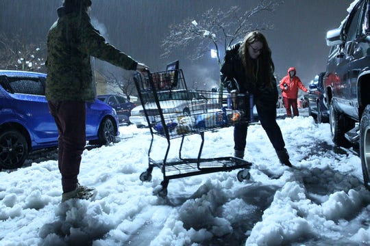 Skyler Alford, left, and his sister, Madison, carry a shopping cart over the snow to their truck so they can load their groceries on Wednesday night, Feb. 13, 2019 in the Safeway parking lot in Anderson. A powerful winter storm dumped a foot of snow in the Northern California city. (Hung T. Vu/Special to the Record Searchlight)