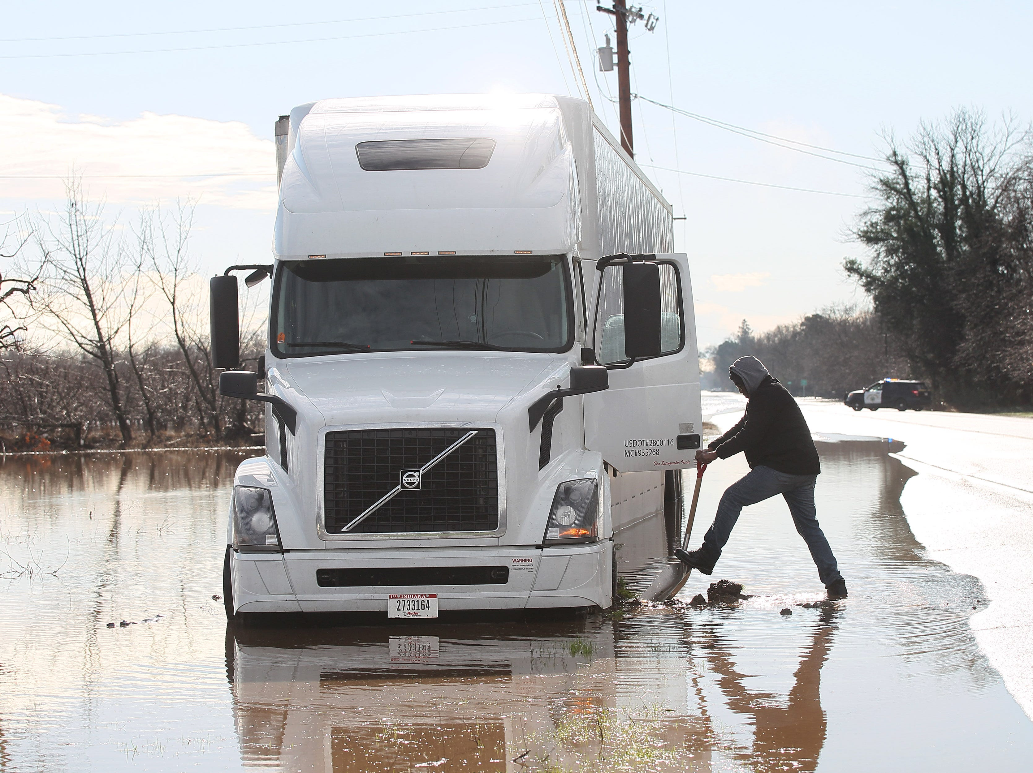 Truck driver, William Shatner,  tries to dig out the mud around the front wheel as his truck got stuck in the flooded area along hwy 99 east of Reb Bluff on Thursday morning.