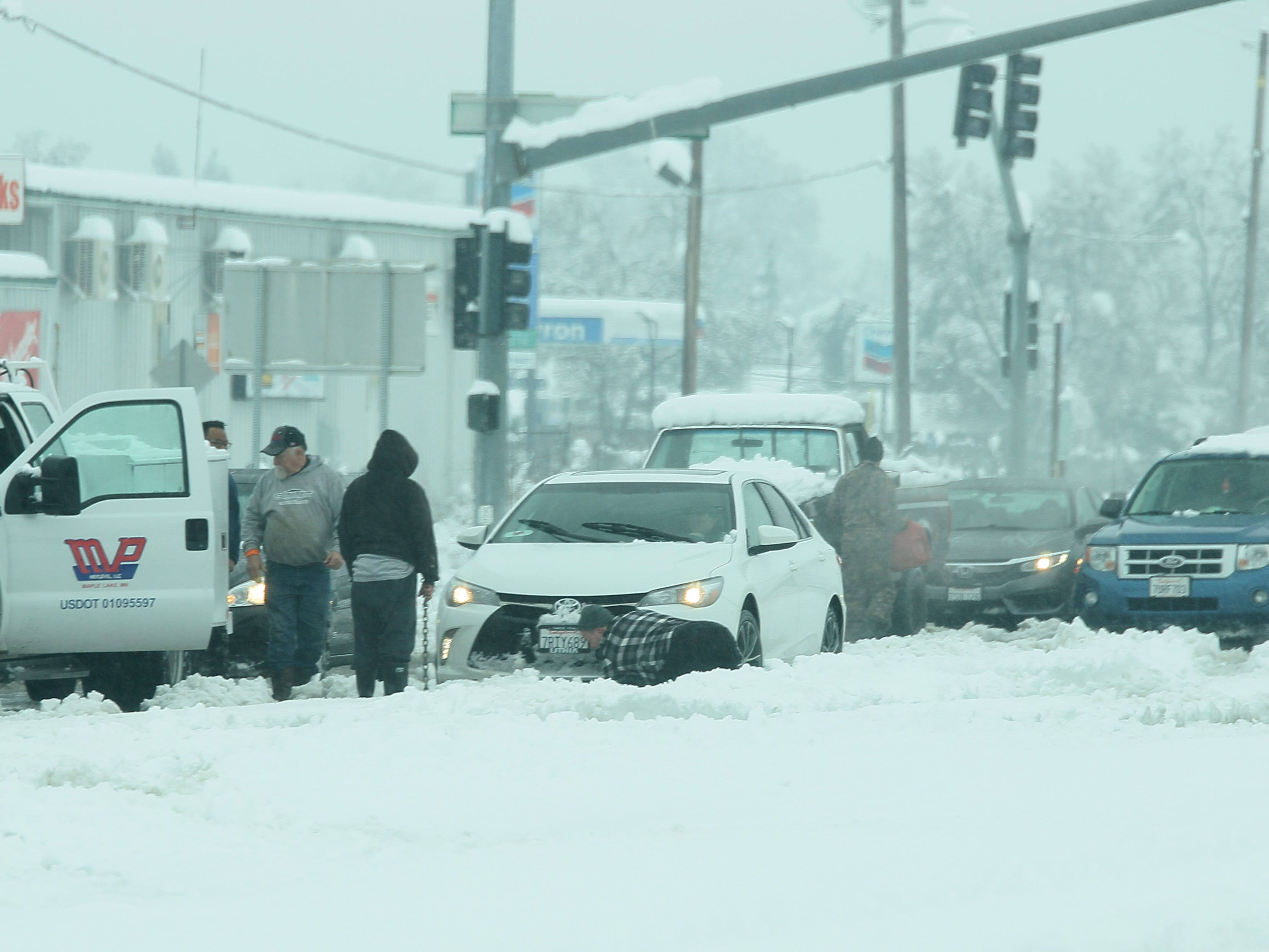 Stranded motorist help each other Wednesday, Feb. 13, 2019 remove their cars from Highway 273 at Deschutes Road in Anderson, California. (Hung T. Vu/Special to the Record Searchlight)
