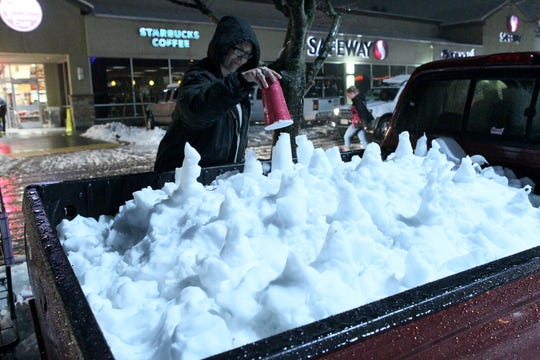 Judy Correia of Redding makes a snow cone with a soda cup in the back of her pick-up truck after stopping at Safeway to do her grocery shopping on Wednesday night, Feb. 13, 2019 in Anderson, California. (Hung T. Vu/Special to the Record Searchlight)