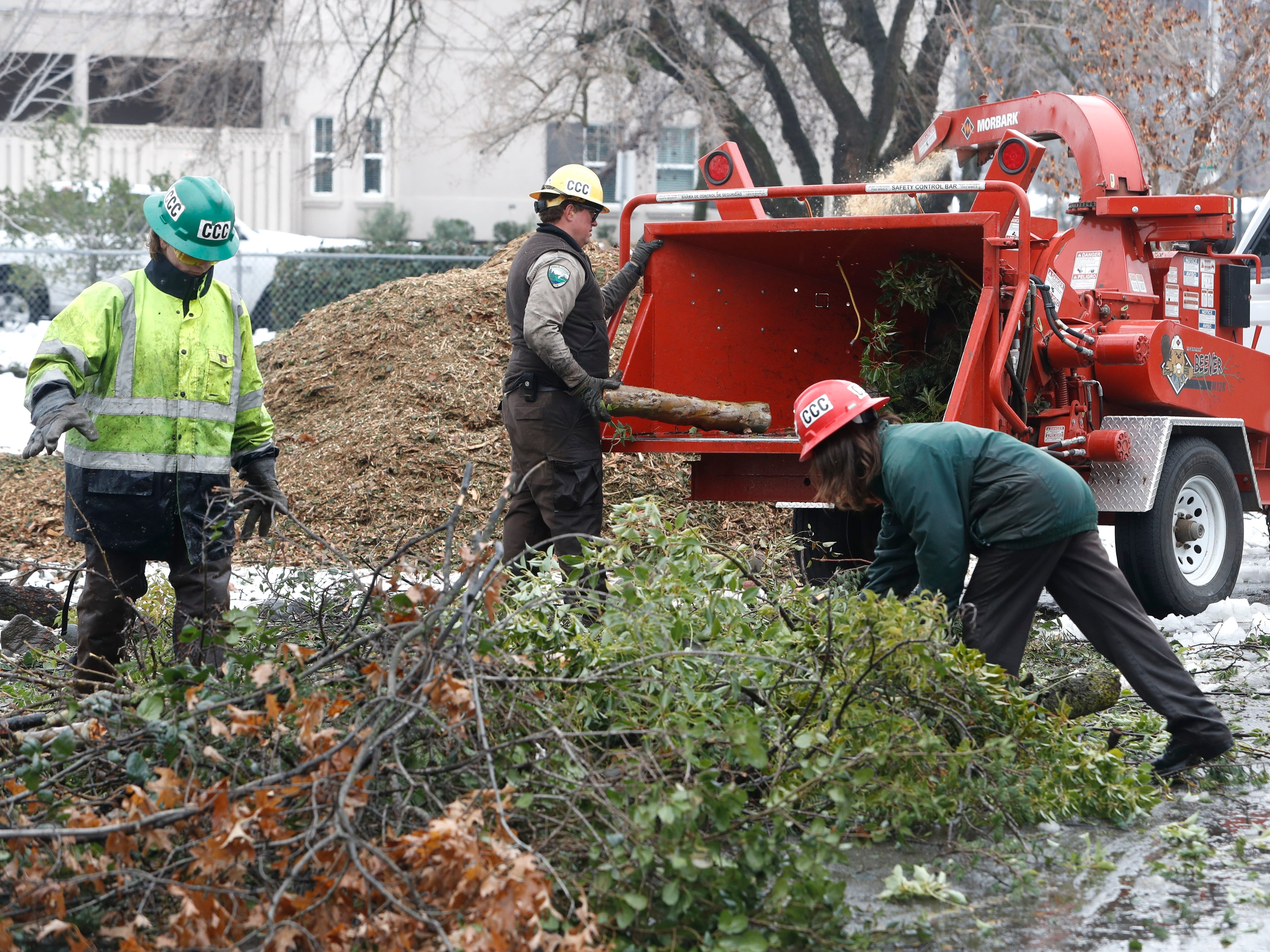 A crew from the Shasta-Cascade California Conservation Corps puts downed tree limbs and brush through a chipper Thursday, Feb. 14, 2019, at Lake Redding Park, which was hard hit by this week's snowstorm.