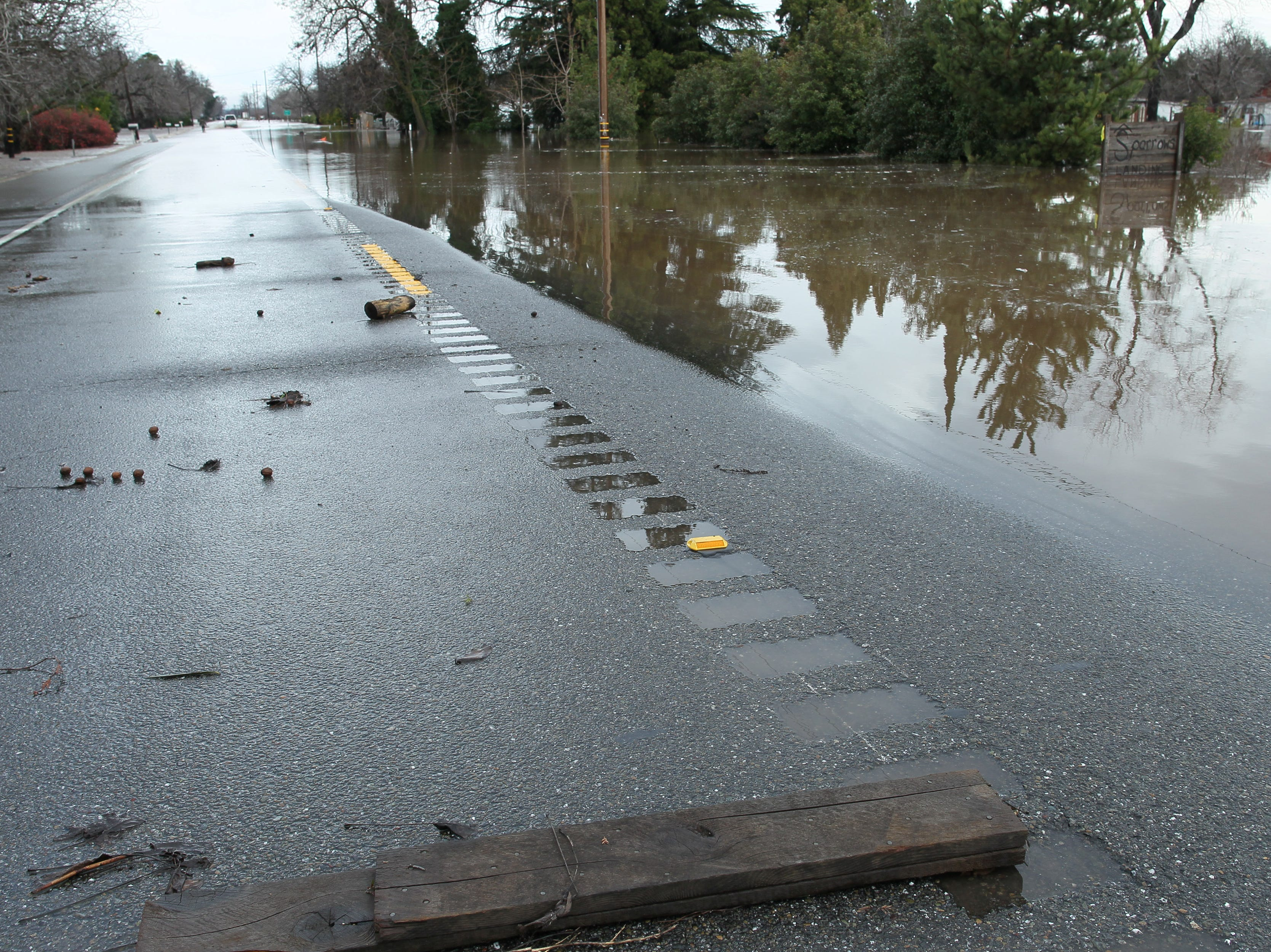 Debris stays on the roadway after the water run across Hwy. 99 east of Red