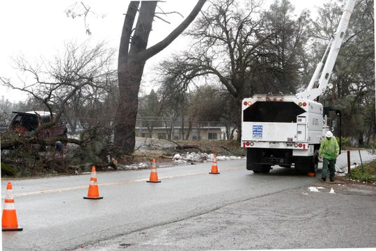 A crew from Utility Crew Service removes branches from power lines along Lake Boulevard in Shasta Lake on Thursday, Feb. 14, 2019. Branches and trees making contact with power lines needed to be moved before electricity could be restored.