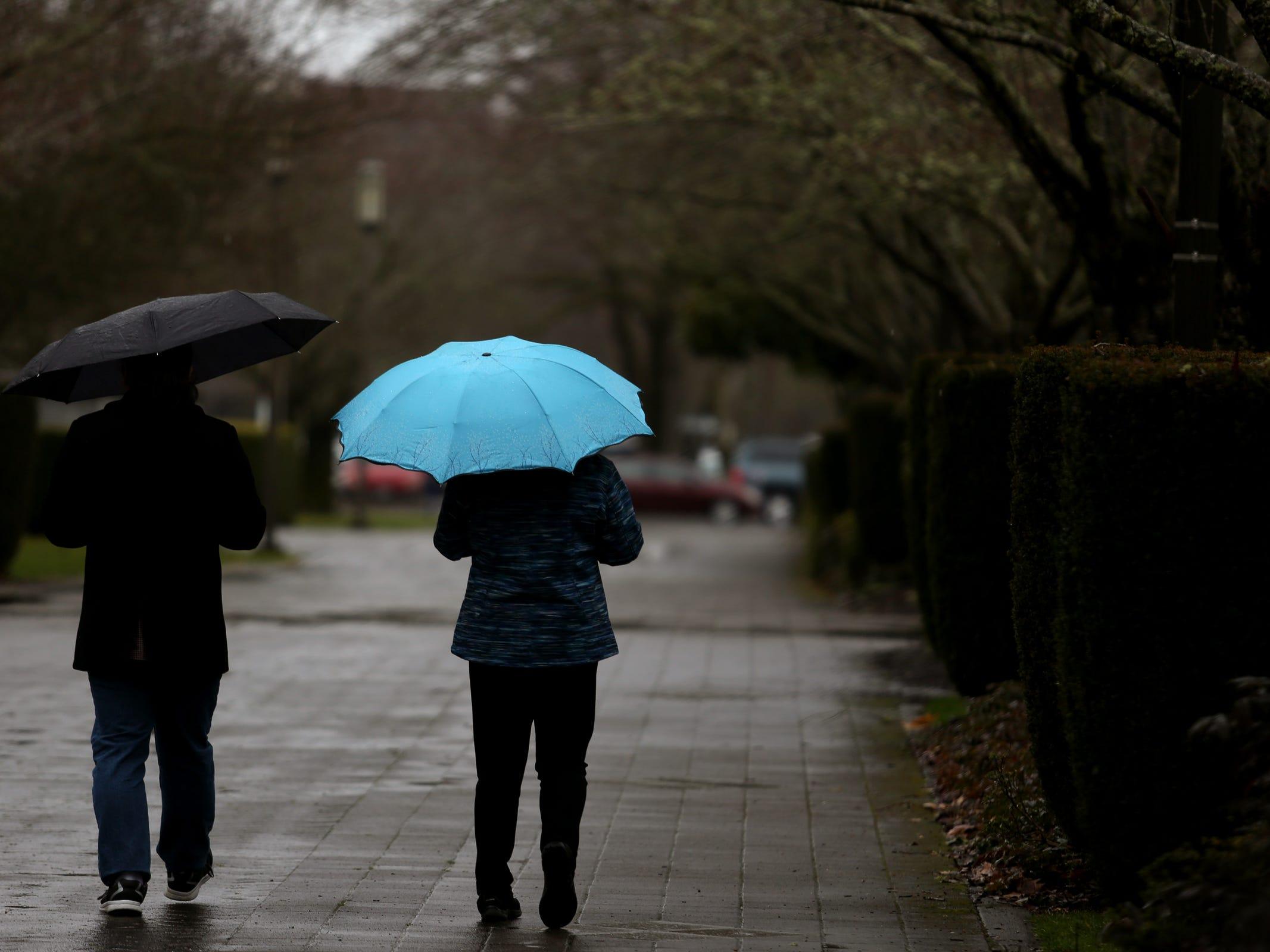People walk with umbrellas as rain falls in Salem on Thursday, Feb. 14, 2019.