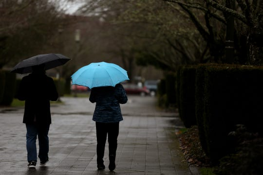 People walk with umbrellas as rain falls in Salem on Thursday, Feb. 14, 2019.